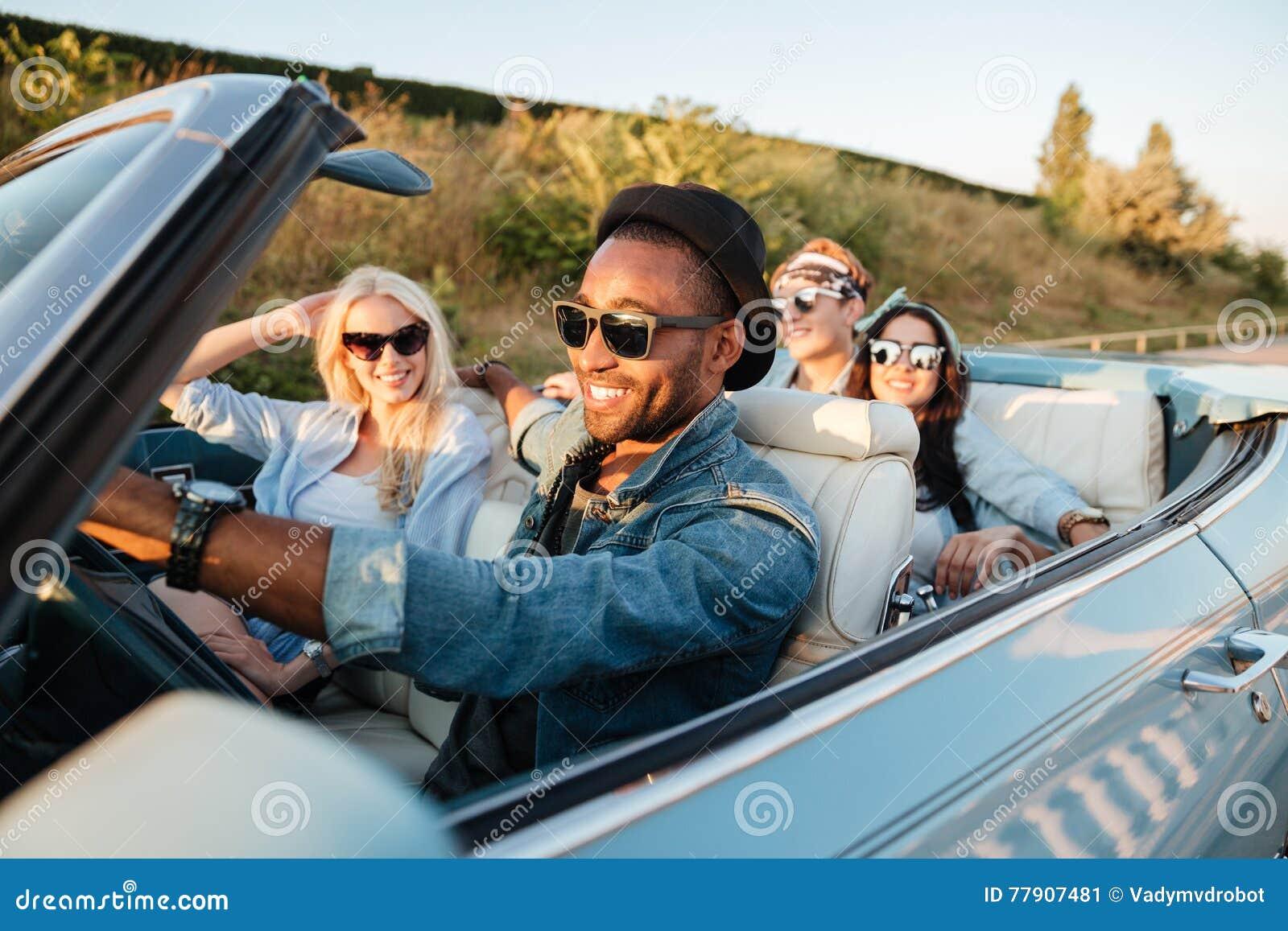 Rozochocony młody przyjaciół jechać samochodowy i ono uśmiecha się w lecie