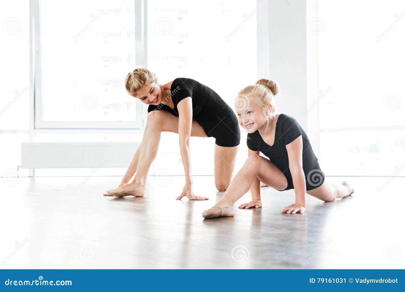 Rozochocony mały baleriny i nauczyciela rozciąganie w balet szkole
