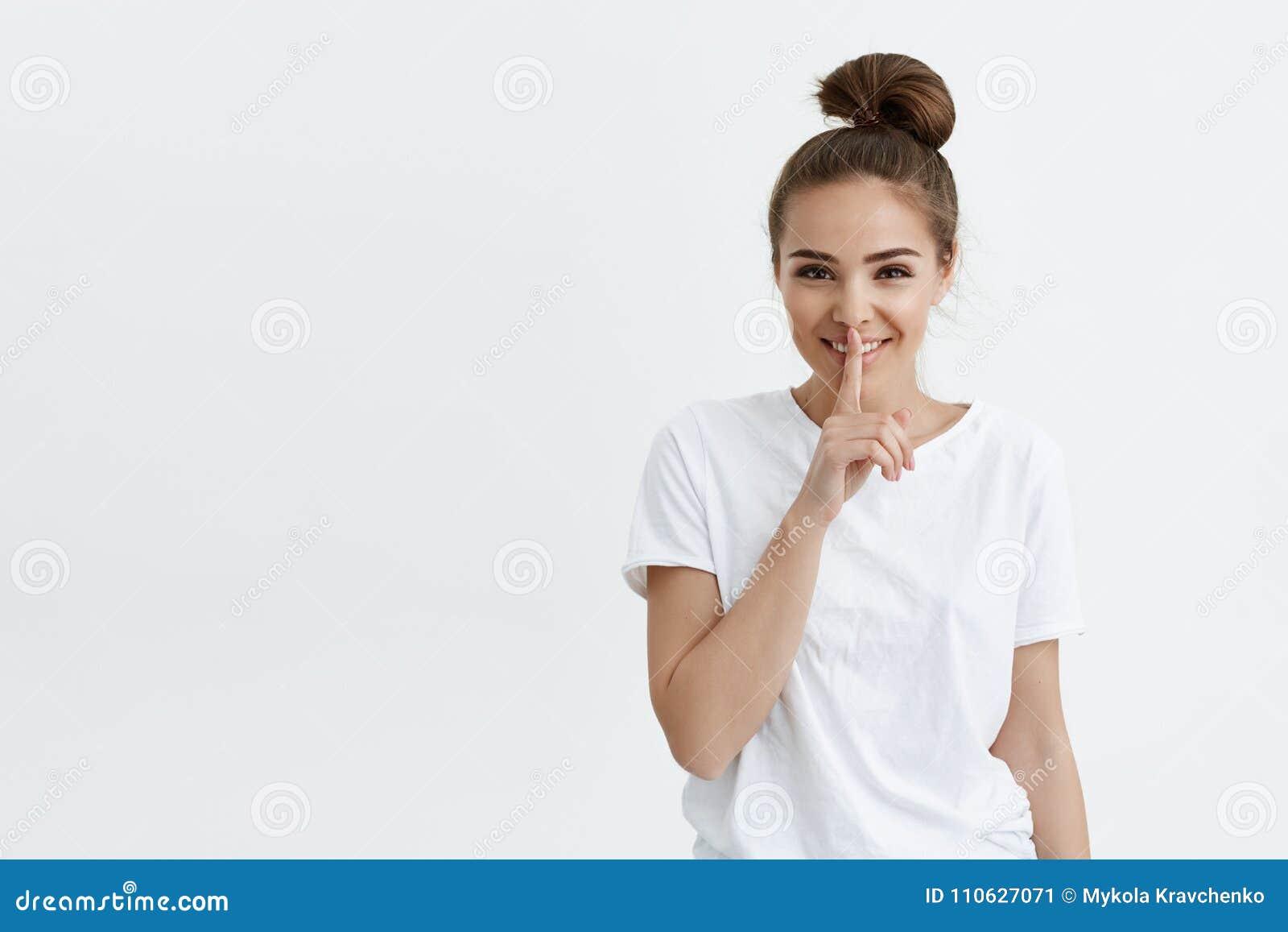 Rozochocony modny europejski żeński ono uśmiecha się, patrzejący z pozytywem podczas gdy pokazywać shh gestykuluje z palcem wskaz