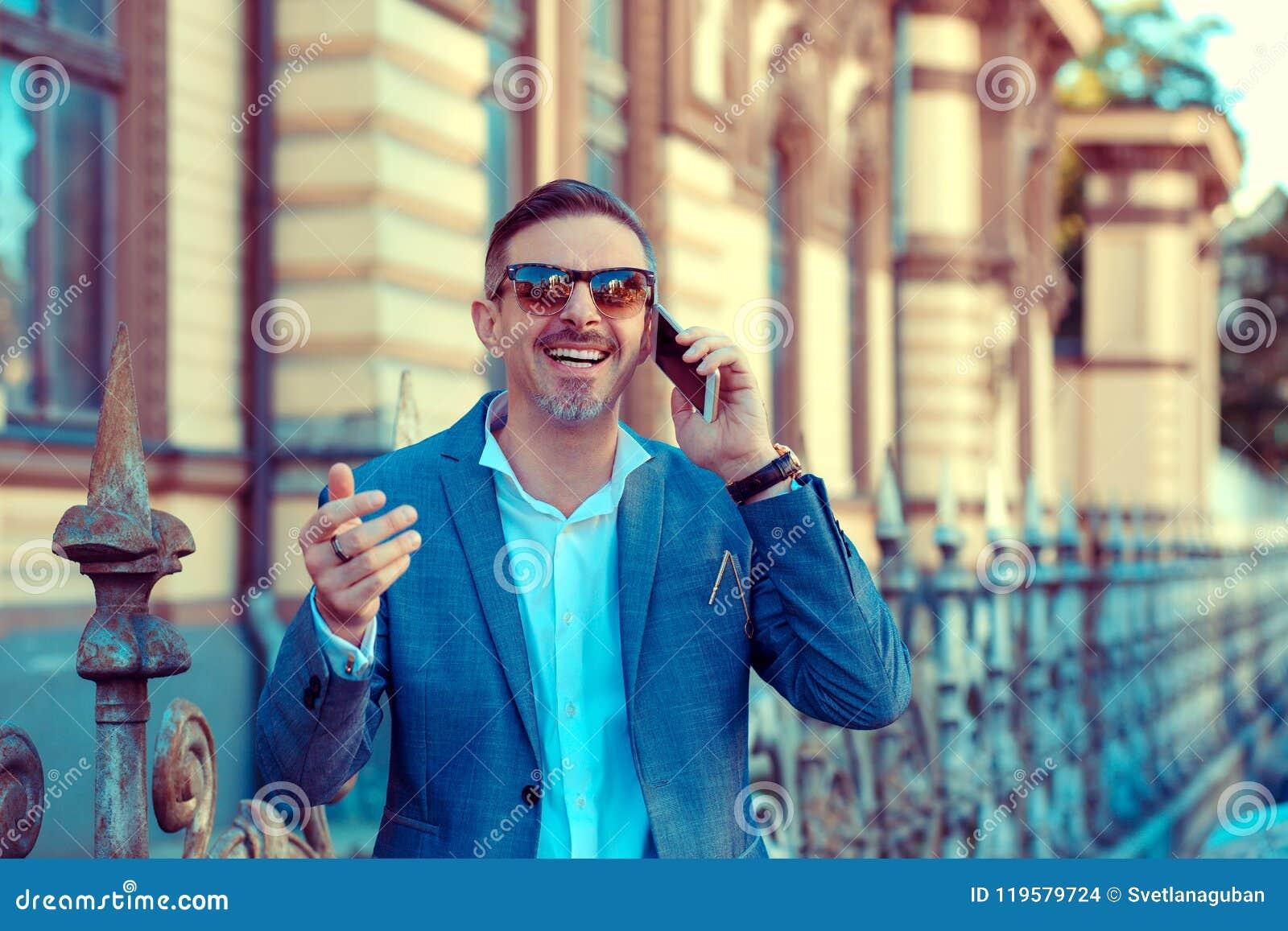 Rozochocony modny mężczyzna ma rozmowę telefonicza outside