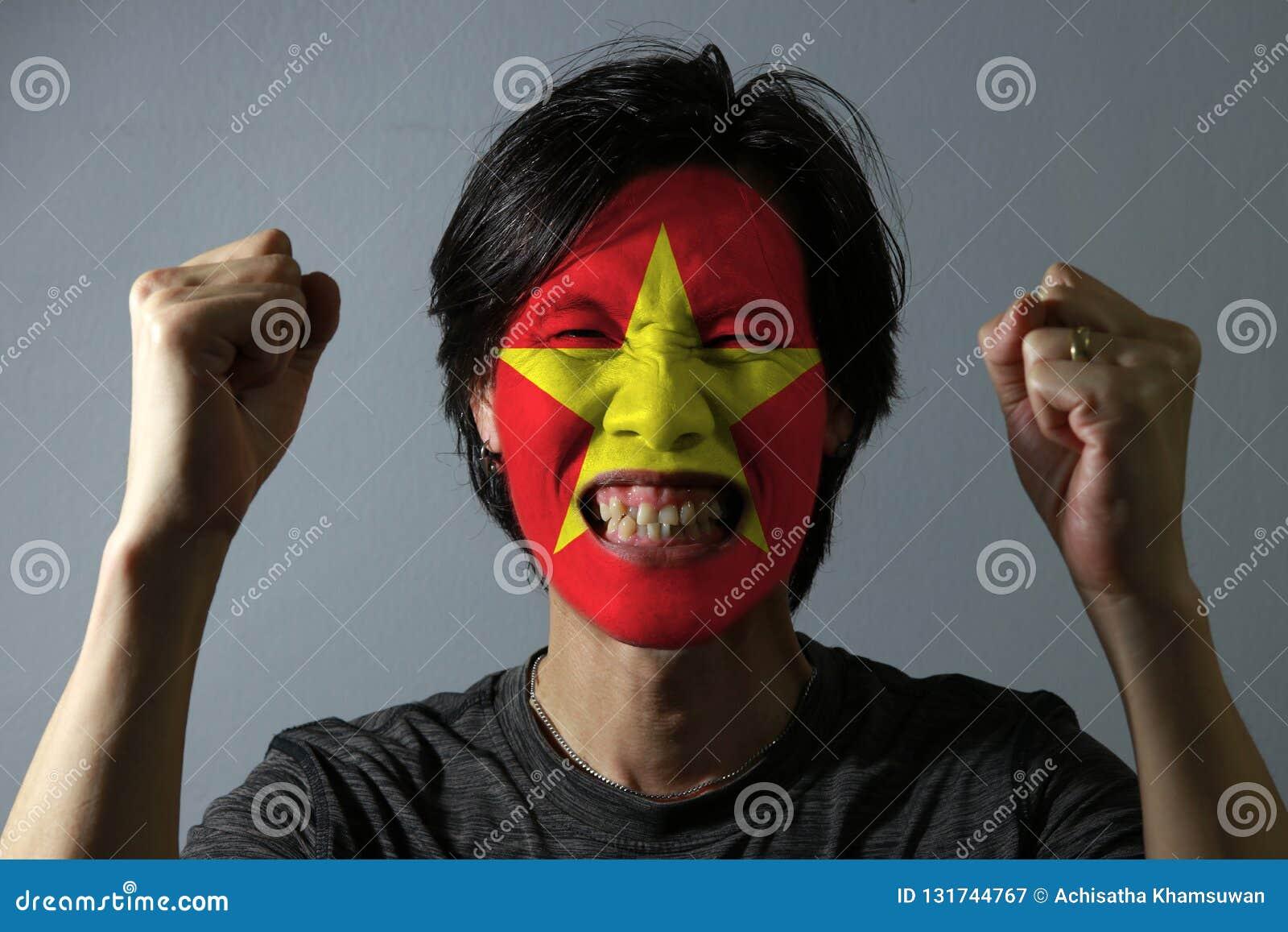 Rozochocony portret mężczyzna z flagą Wietnam malował na jego twarzy na popielatym tle