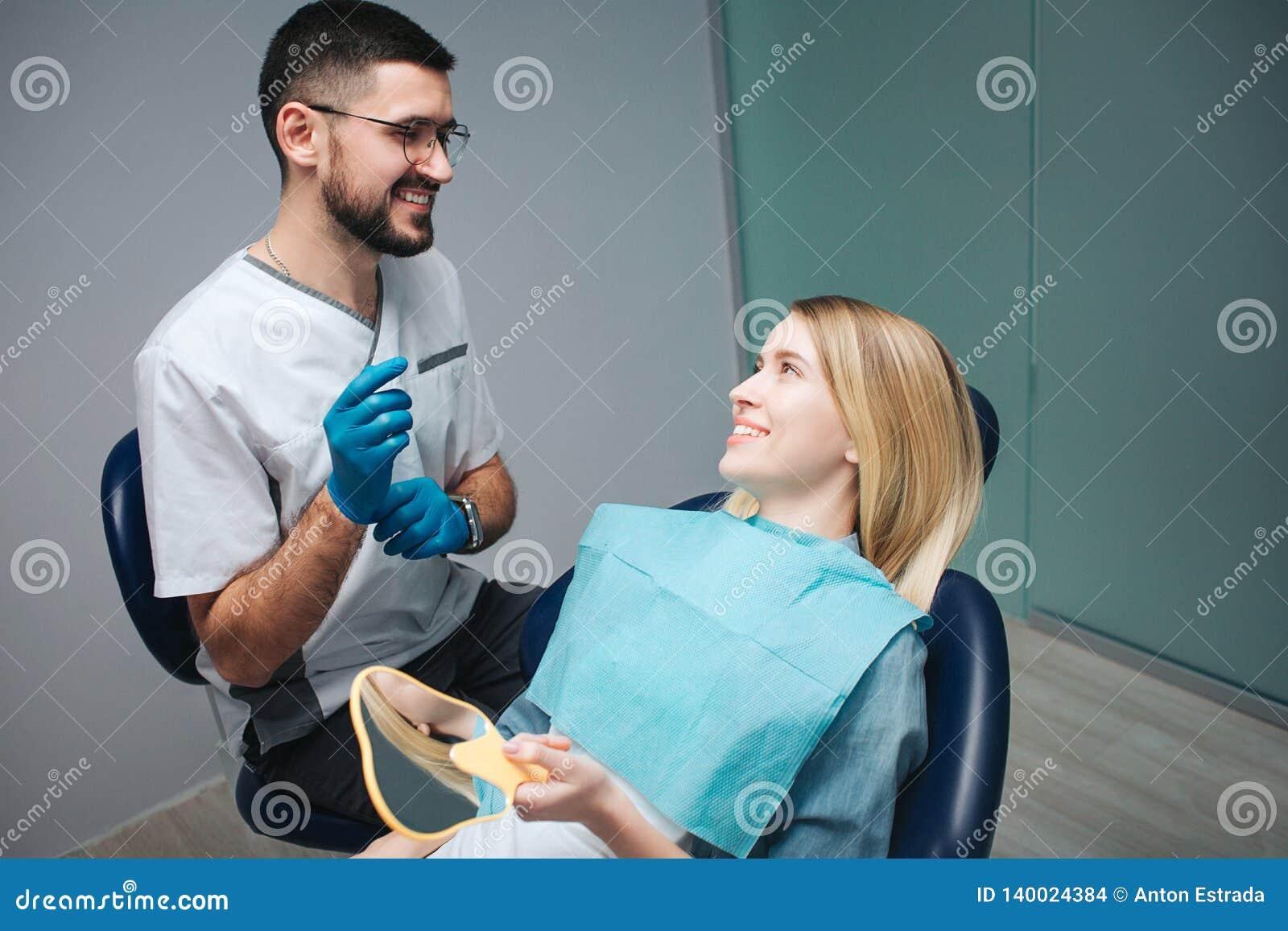 Rozochocony pozytywny dentysta i klient w dentystyce tło biel spojrzenie biel uśmiechu biel Żeński klient siedzi w krześle i