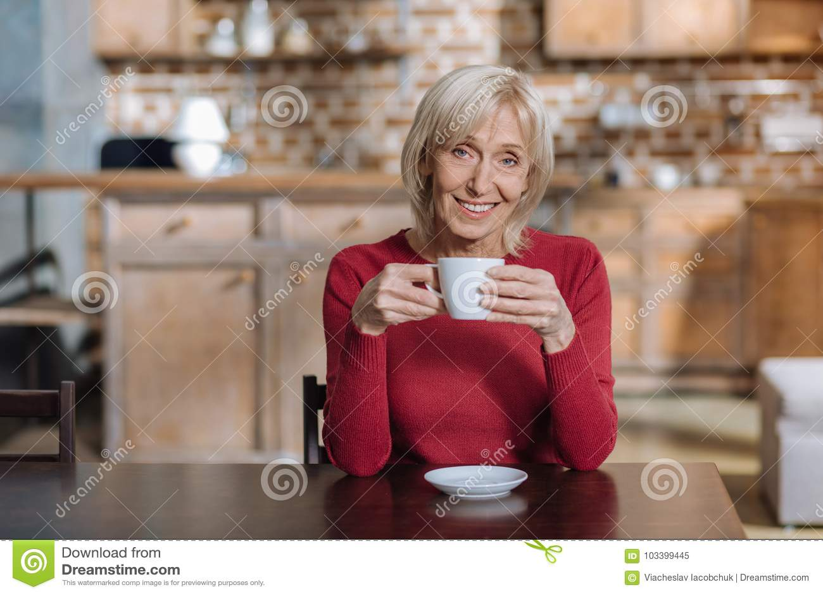 Rozochocony pozytywny starszy kobiety pić herbaciany i uśmiechnięty