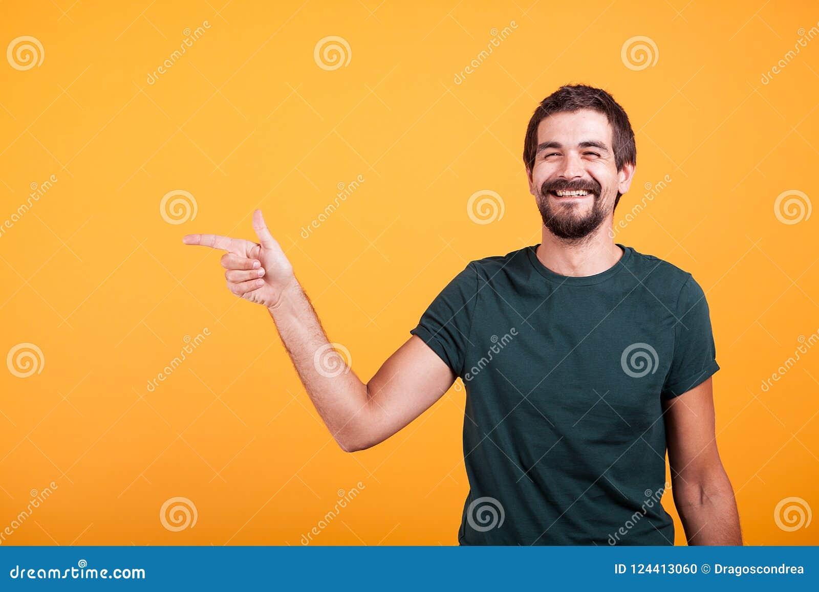 Rozochocony uśmiechnięty mężczyzna wskazuje przy jego dobrze przy copyspace