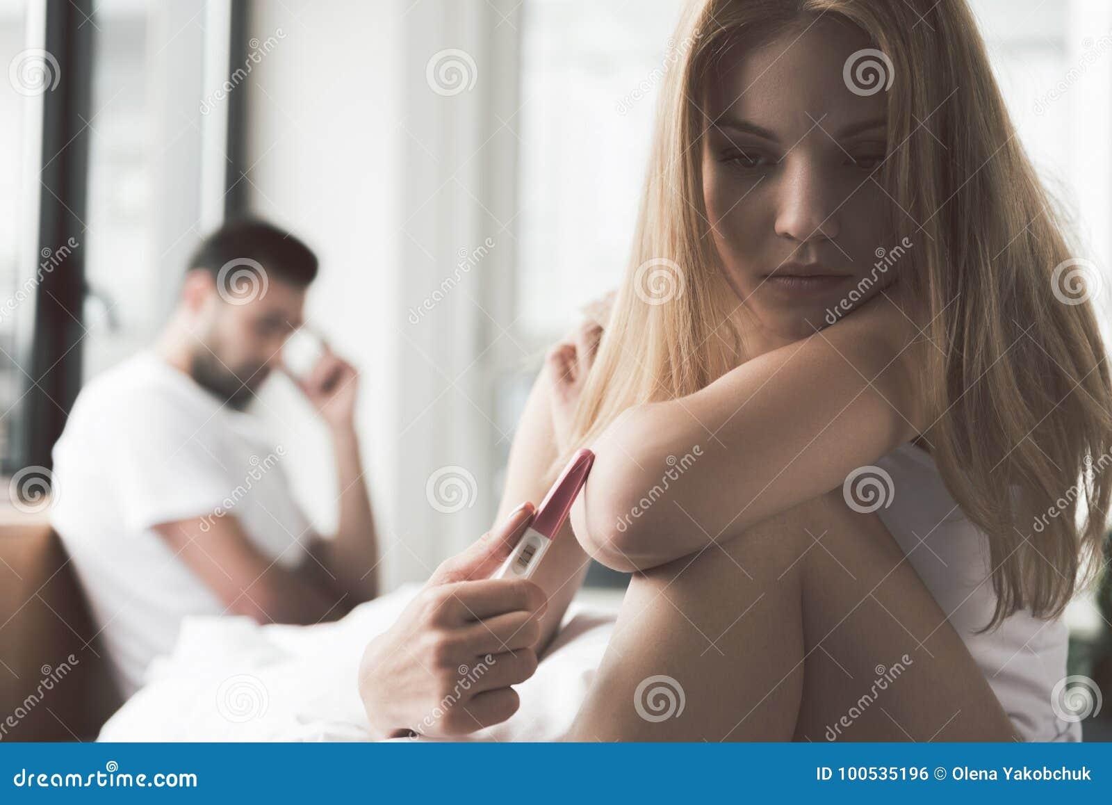Rozpaczająca młoda kobieta trzyma ciążowego test z dwa paskami