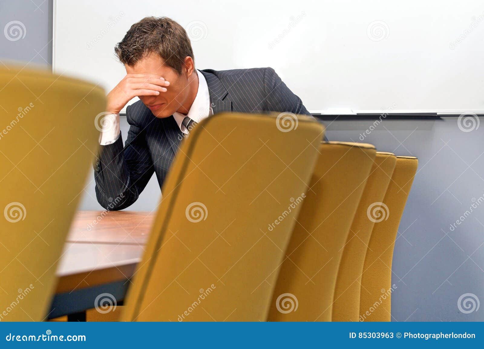 Rozpaczający biznesmena obsiadanie w biurze