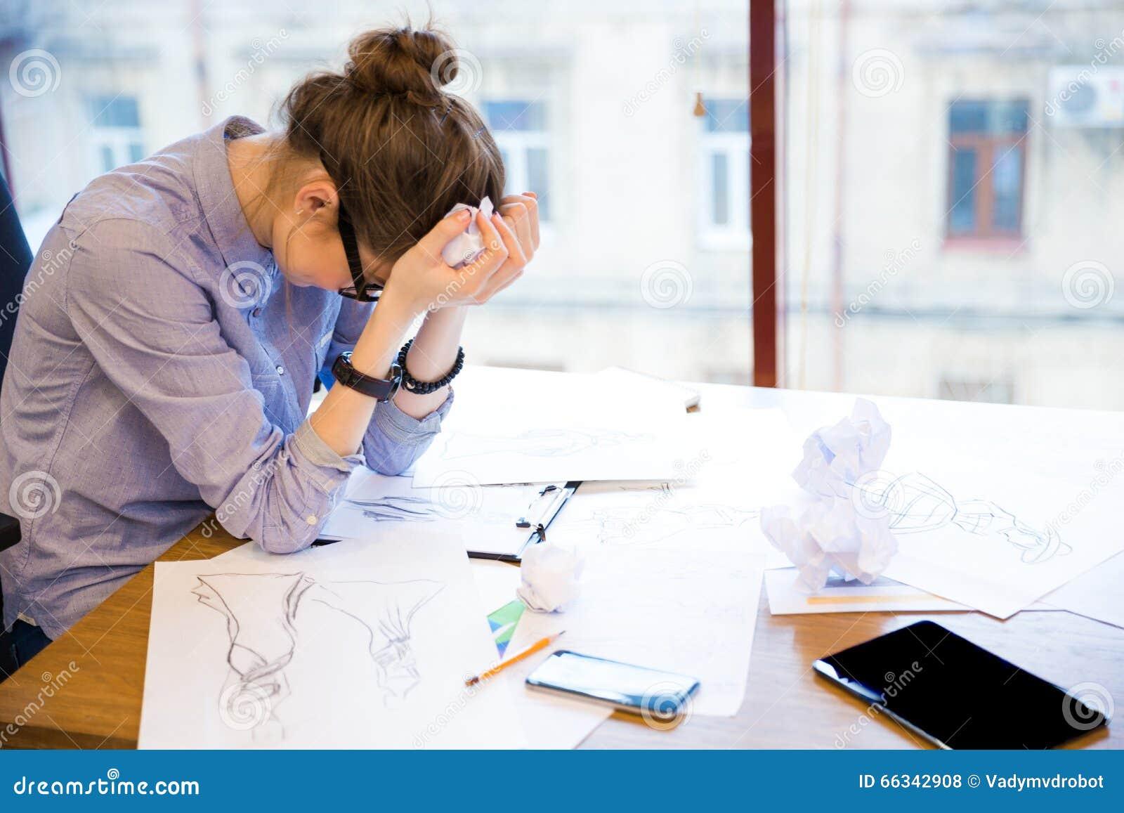 Rozpaczający kobieta projektanta mody obsiadanie w biurze z nakreśleniami