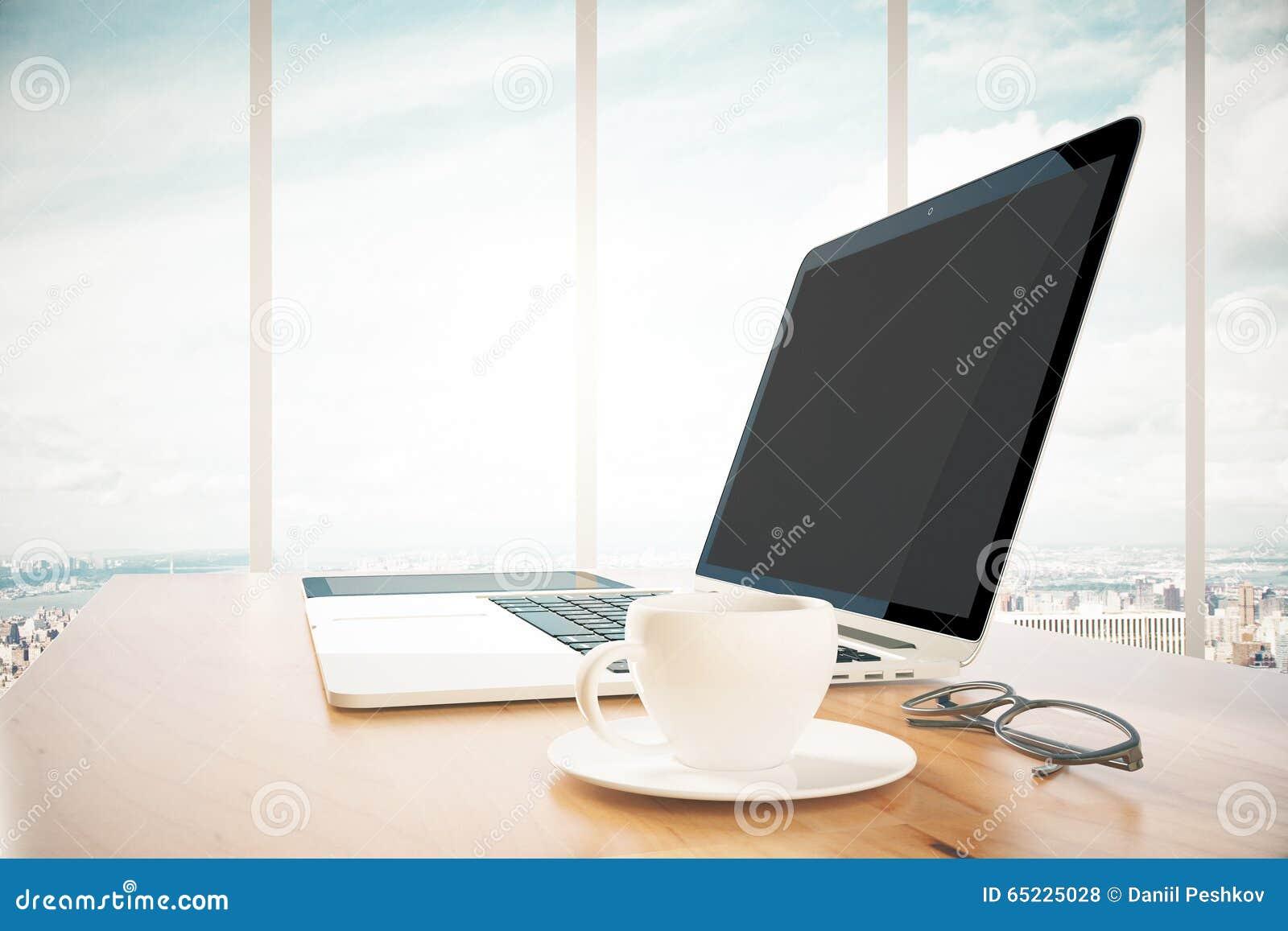 Rozpieczętowany laptop z filiżanką cooffee na drewnianym stole w biurze