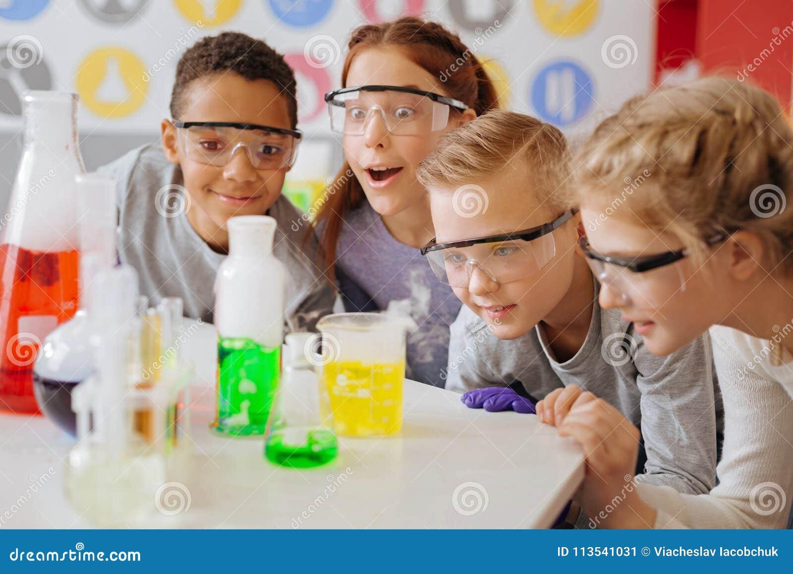 Rozradowani nastoletni ucznie obserwuje fazę końcową chemiczny eksperyment