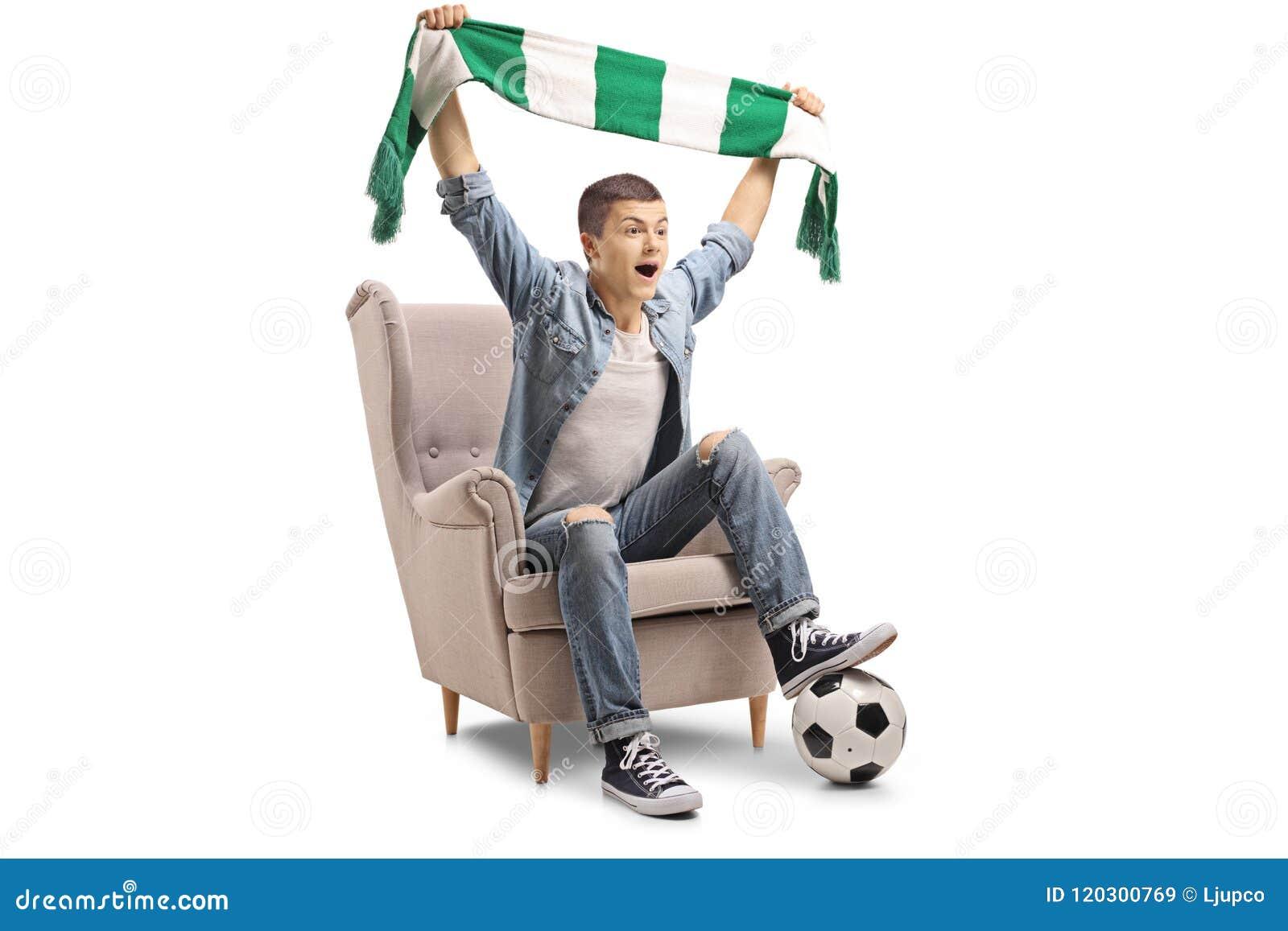 Rozradowany nastoletni piłki nożnej fan z szalikiem i futbolowym obsiadaniem