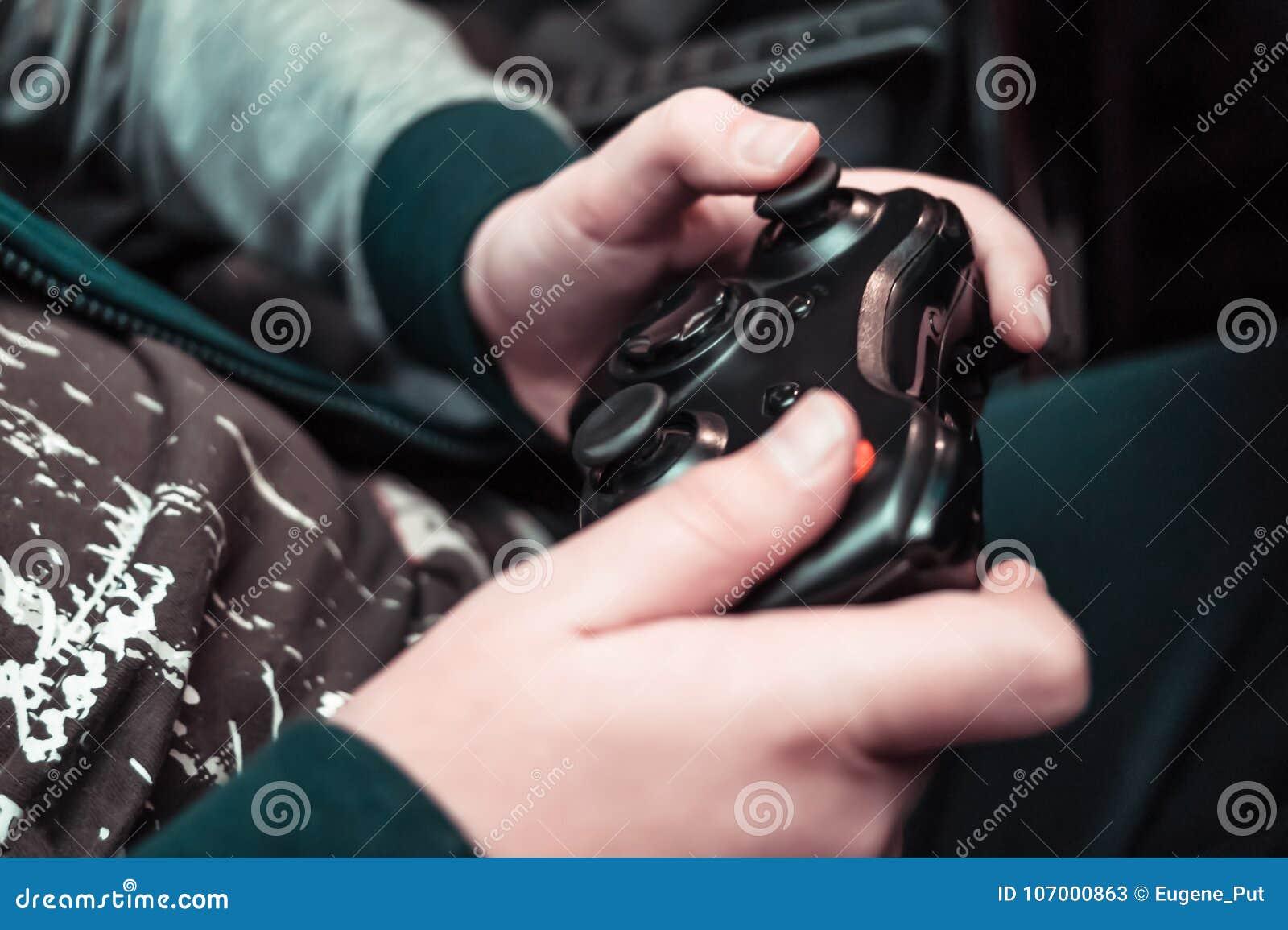 Rozrywka, domowe elektronika, hazardu pojęcie: nastolatek wręcza mieniu bezprzewodowego kontrolera gamepad bawić się konsolę wide