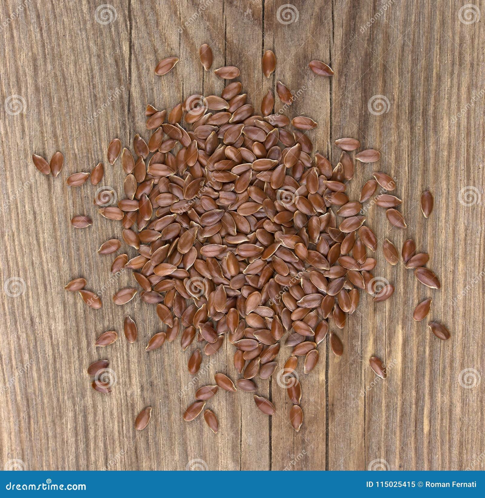 Rozrzuceni lnów ziarna na drewnianym tle