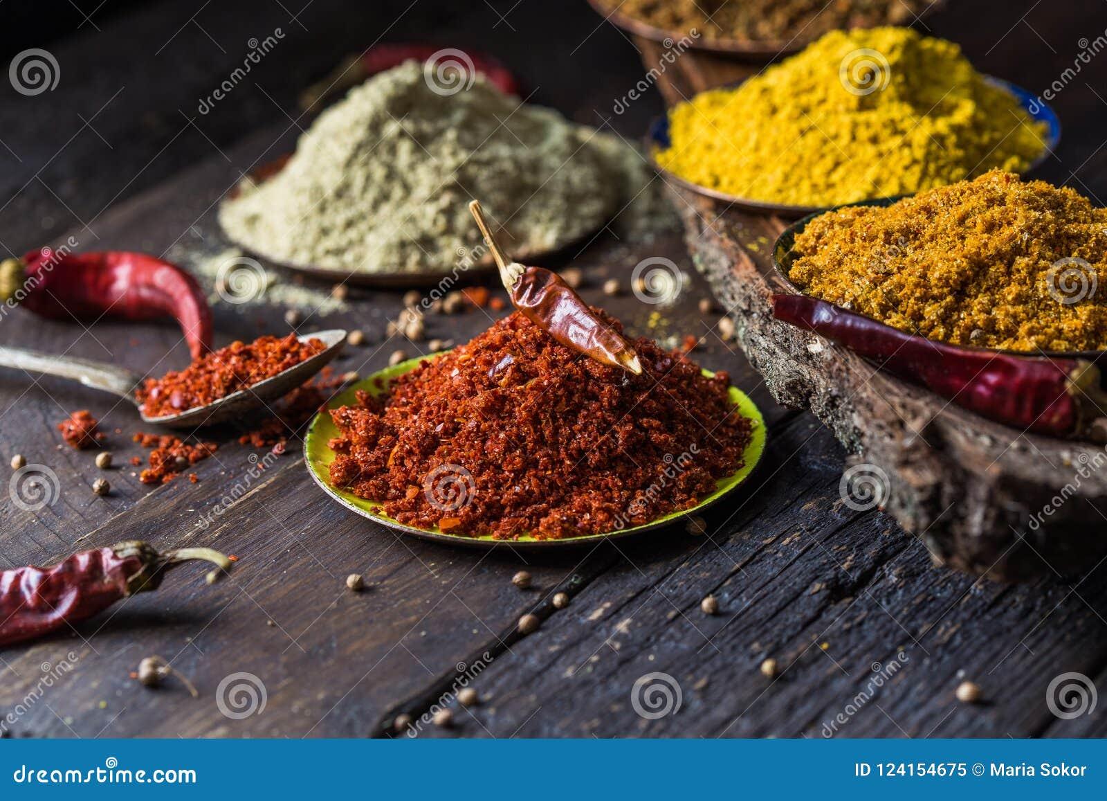 Rozsypiska różnorodne zmielone pikantność na drewnianym tle Gruzińskie pikantność, Indiańskie pikantność, Arabskie pikantność Pik