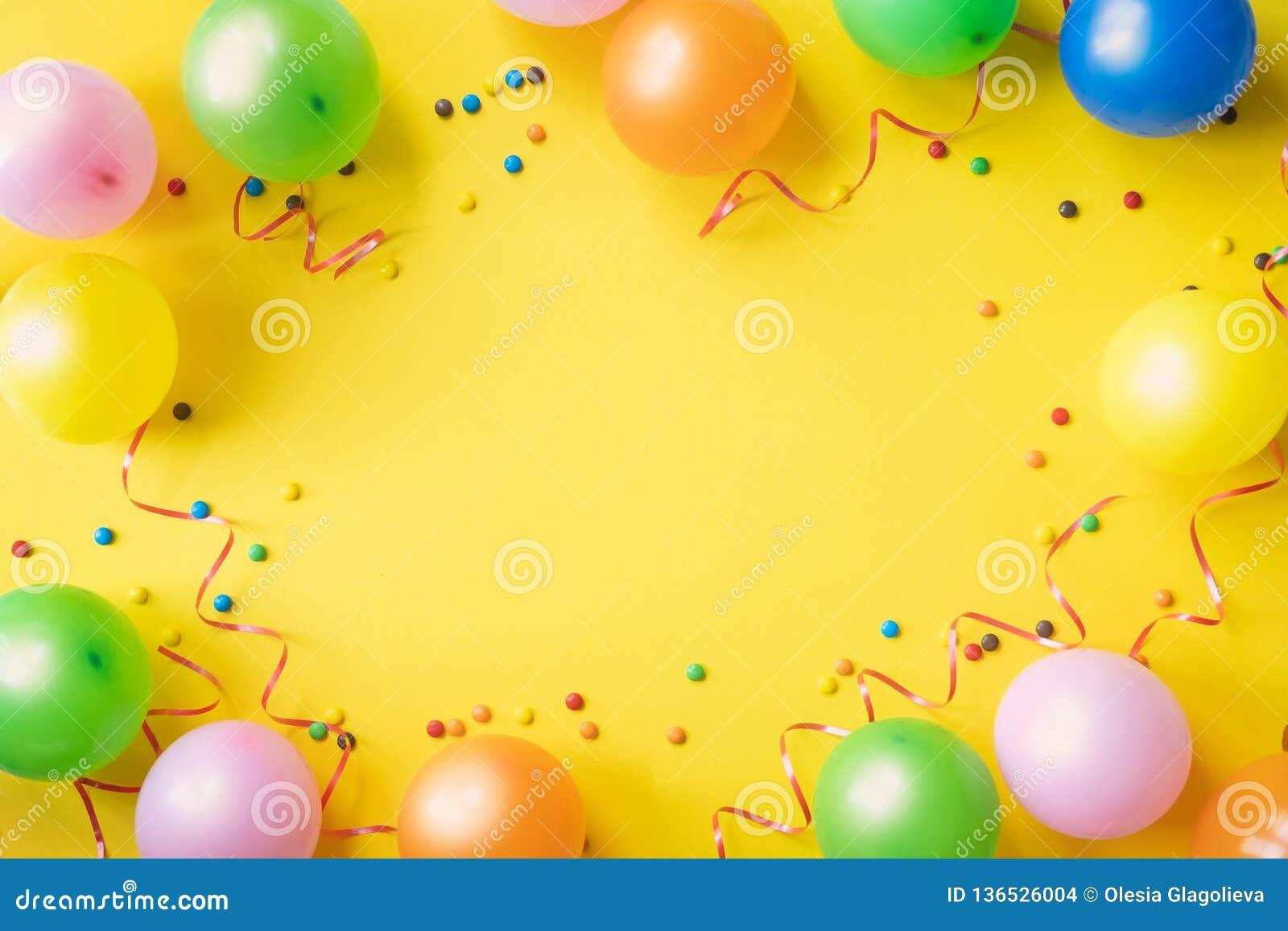Rozsypisko kolorowi balony, confetti i cukierki na żółtym stołowym odgórnym widoku, Przyjęcia urodzinowego tło Świąteczny kartka