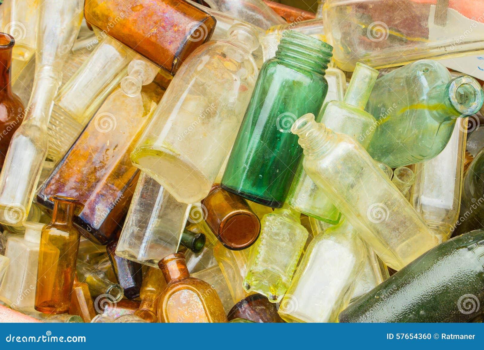 Rozsypisko stary brudzi butelki dla sprzedaży przy bazarem jako tło