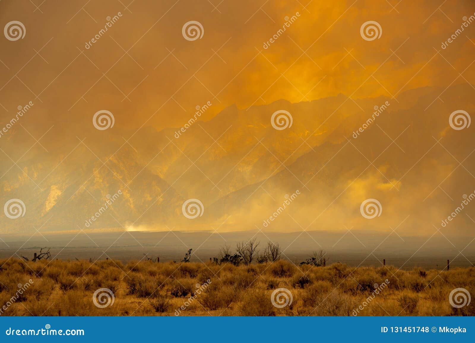 Rozszalały pożar rozdziera przez Sierra Nevada gór w Kalifornia, obraca niebo w blask pomarańcze dym