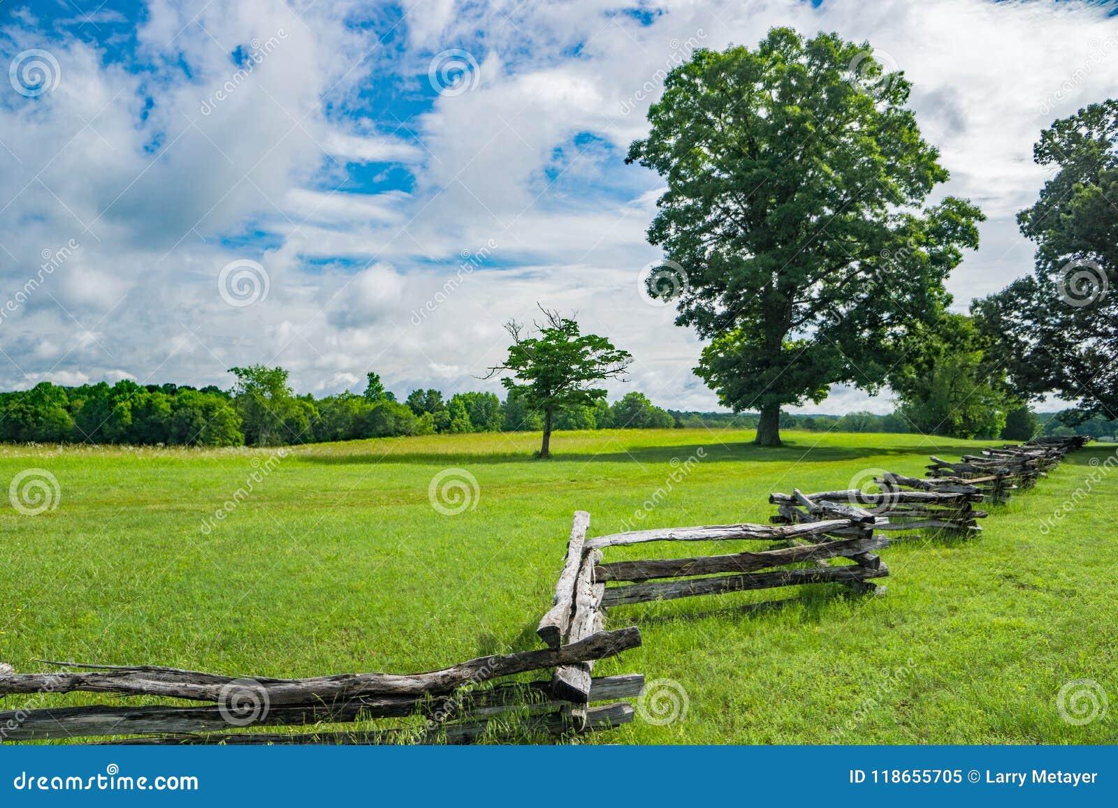 Rozszczepiony Sztachetowy ogrodzenie w polu na Pięknym wiosna dniu