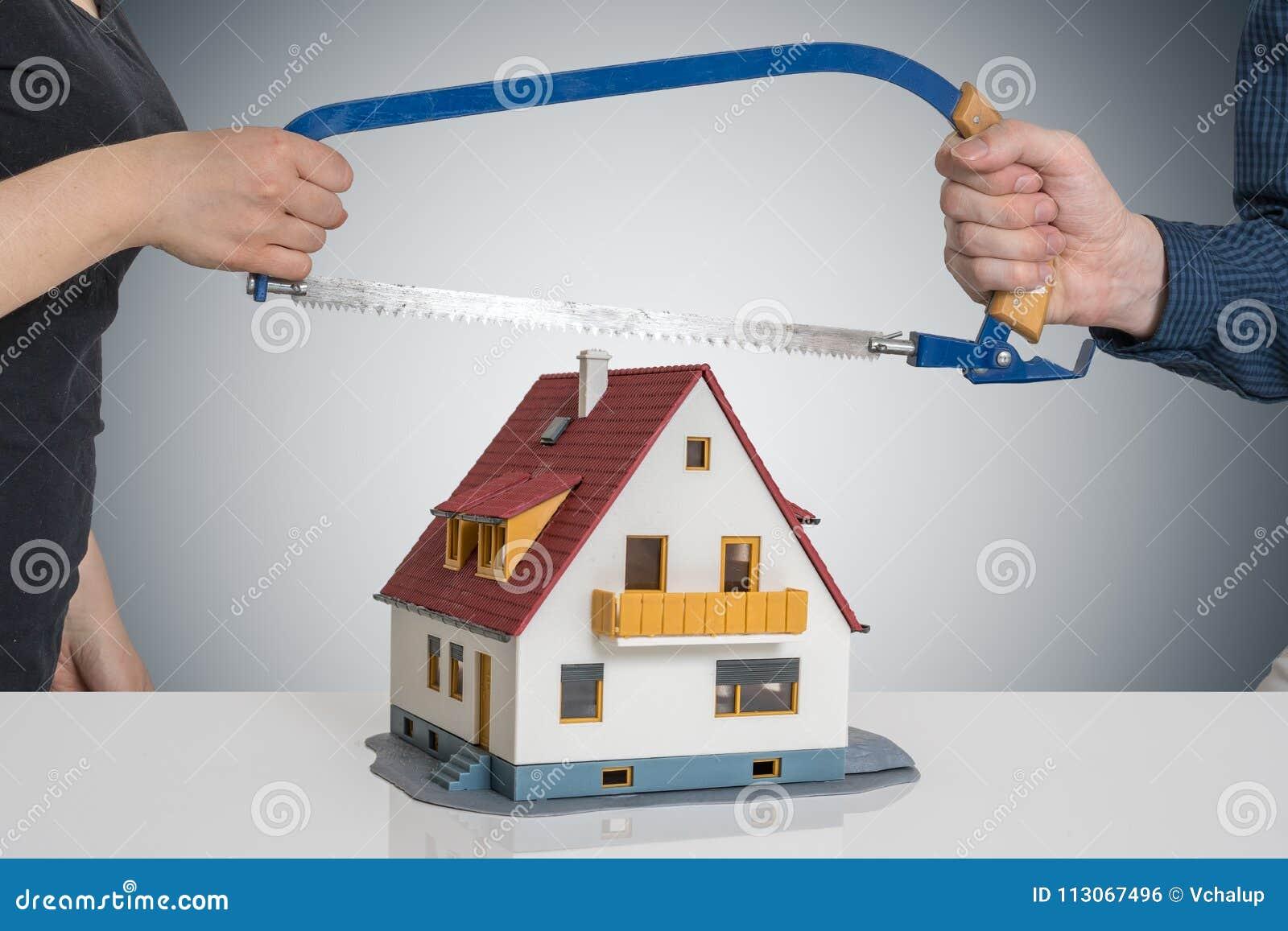 Rozwód i ćwiartowanie domowy pojęcie Mężczyzna i kobieta rozszczepiamy modela dom z zobaczyliśmy