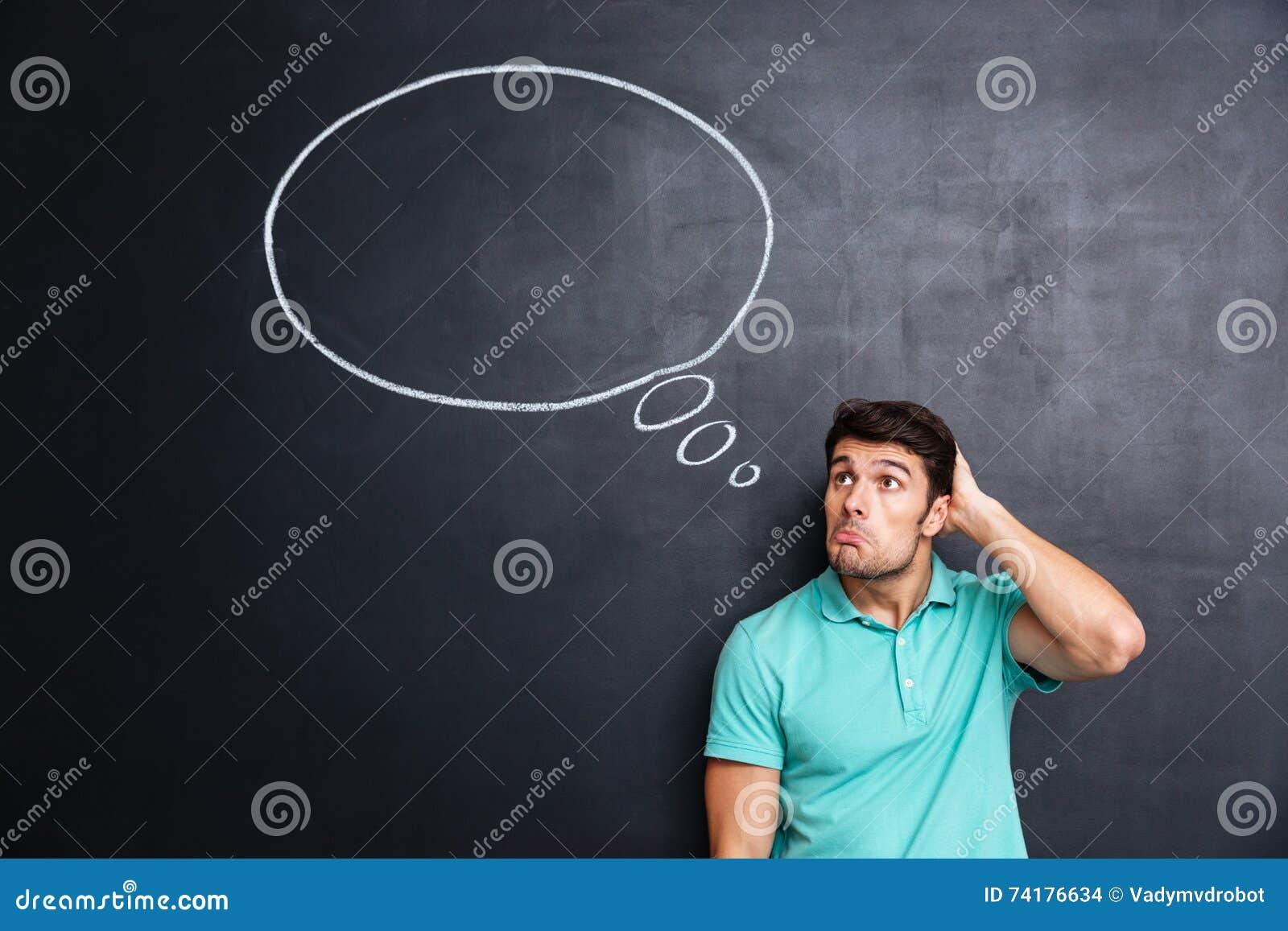 Rozważna zmieszana młody człowiek pozycja, główkowanie nad blackboard tłem i