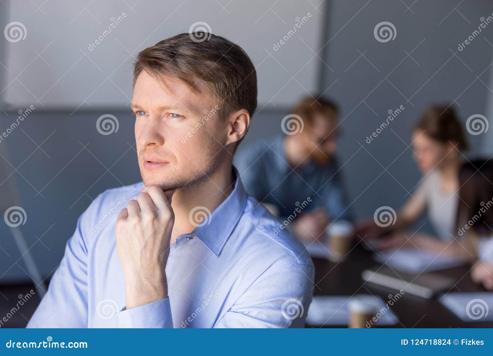 Rozważni męscy pracowników spojrzenia w dystansowym główkowaniu o succes