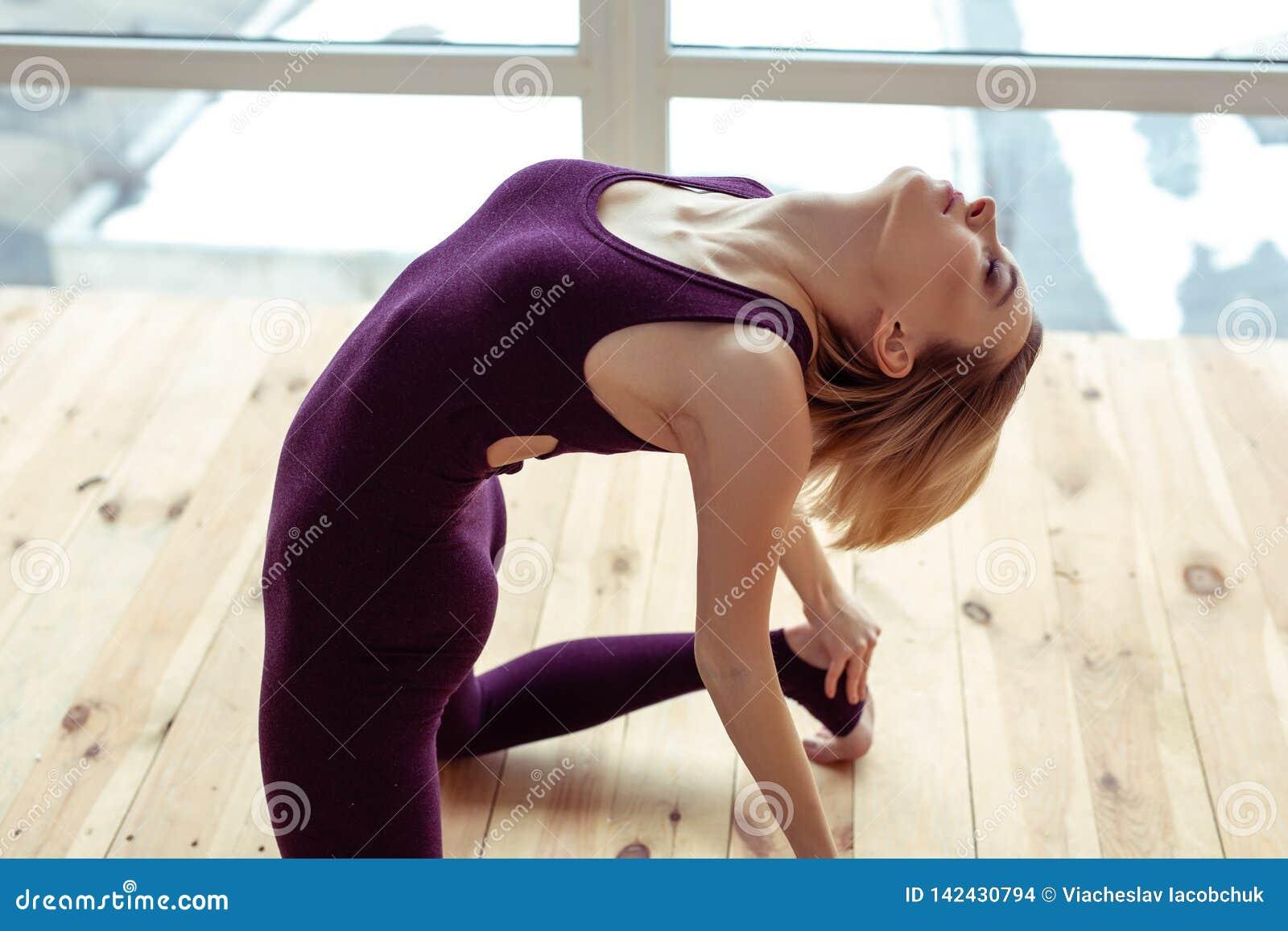 Rozważny atrakcyjnej kobiety obsiadanie na nagiej drewnianej podłodze