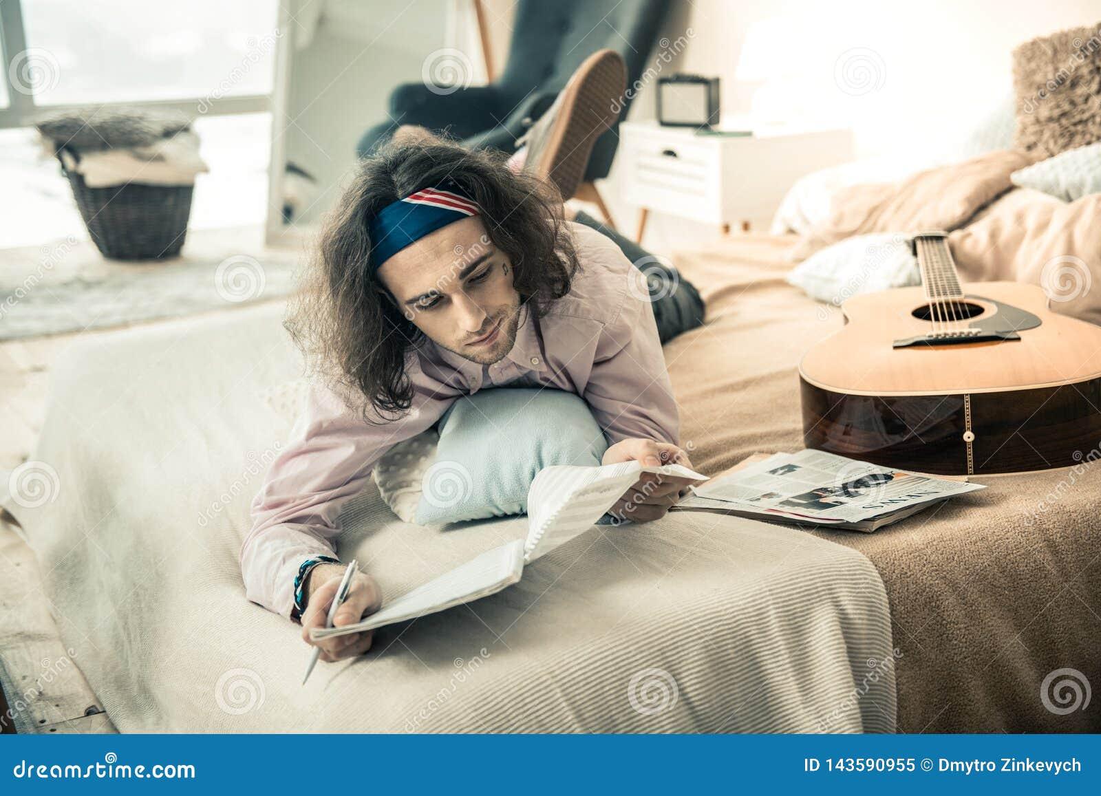 Rozważny młody człowiek obserwuje notatki w specjalnym albumu w kolorowych bandanach