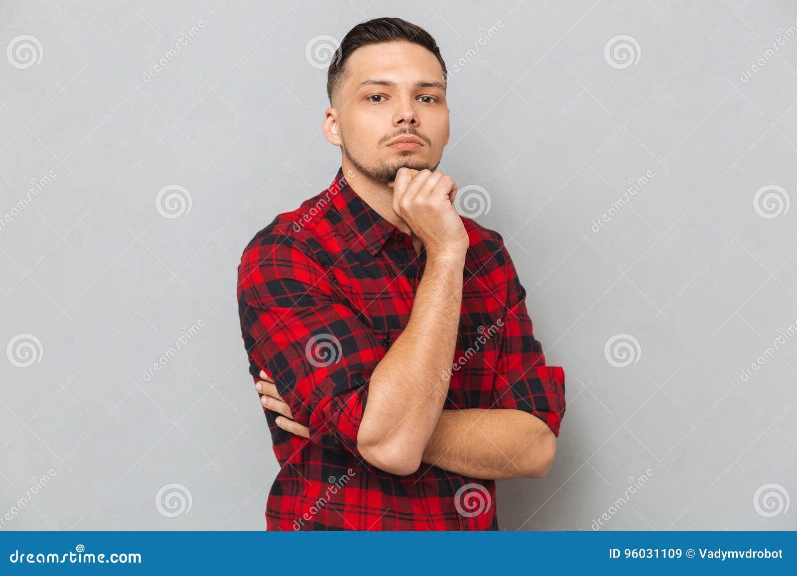 Rozważny młody człowiek patrzeje kamerę