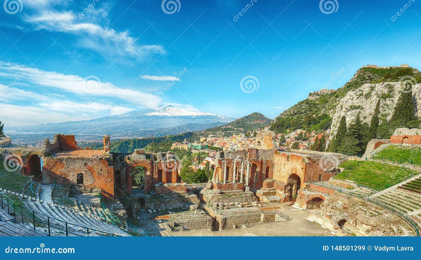 Ruínas do teatro do grego clássico no vulcão de Taormina e de Etna no fundo