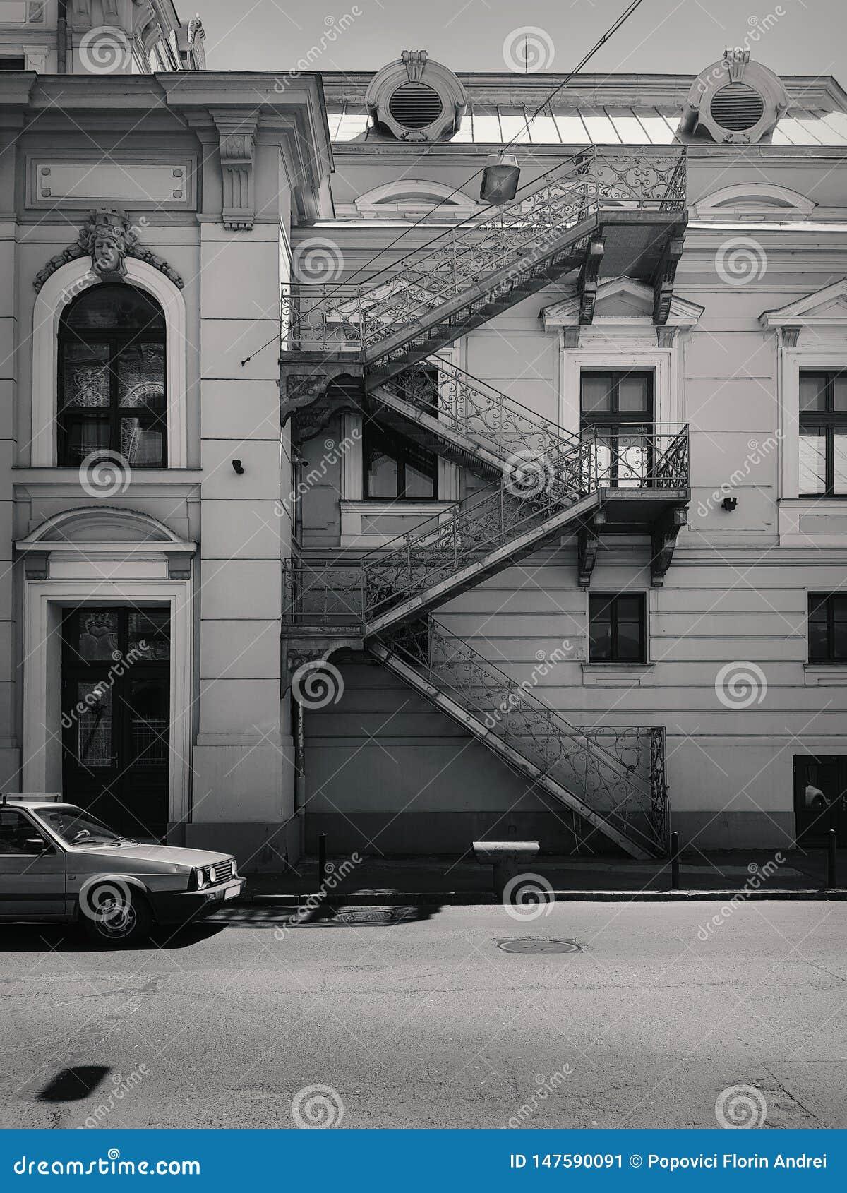 Rua com construção velha e um carro, em preto e branco