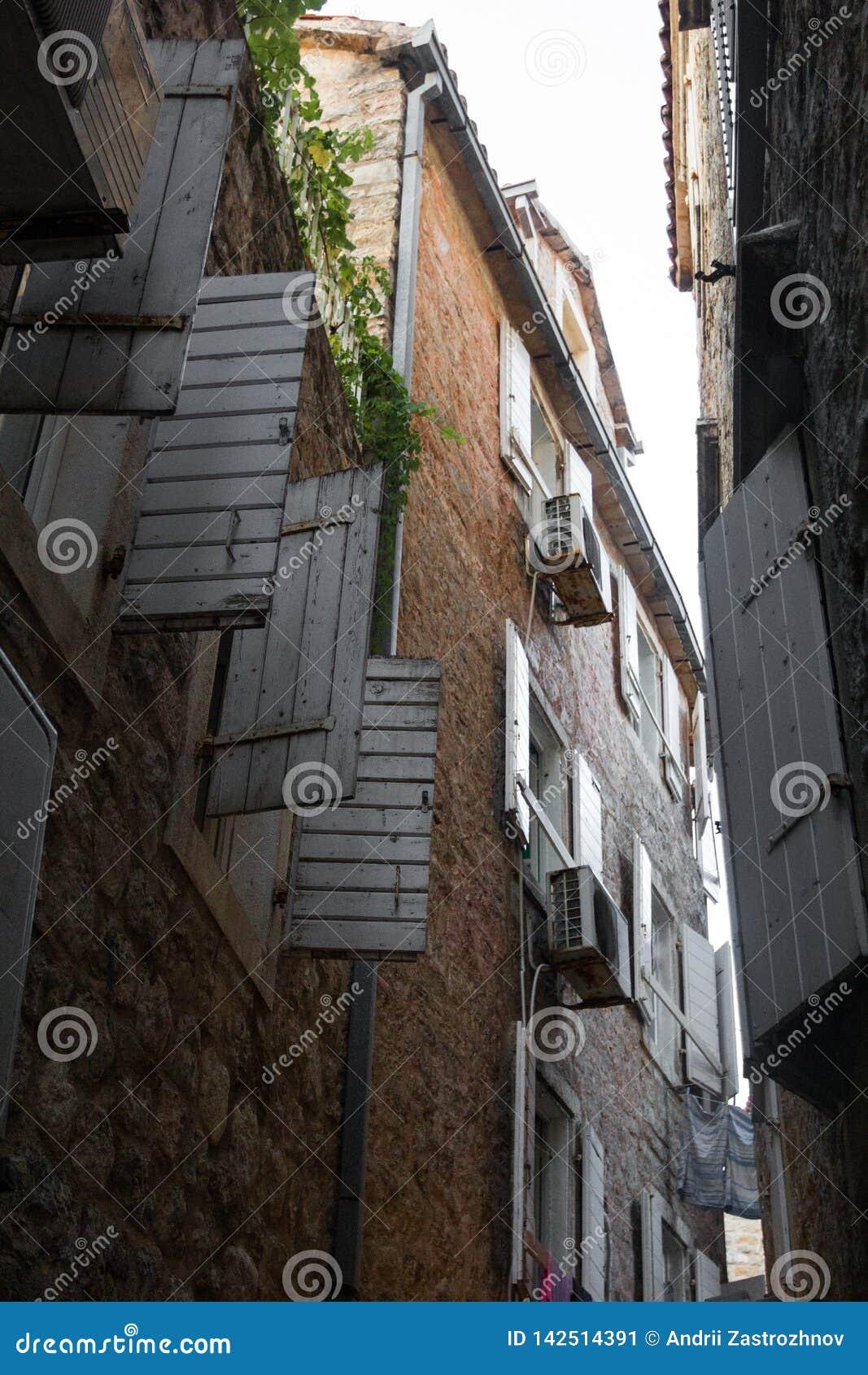 A rua estreita velha, a vista em cima Obturadores da janela aberta