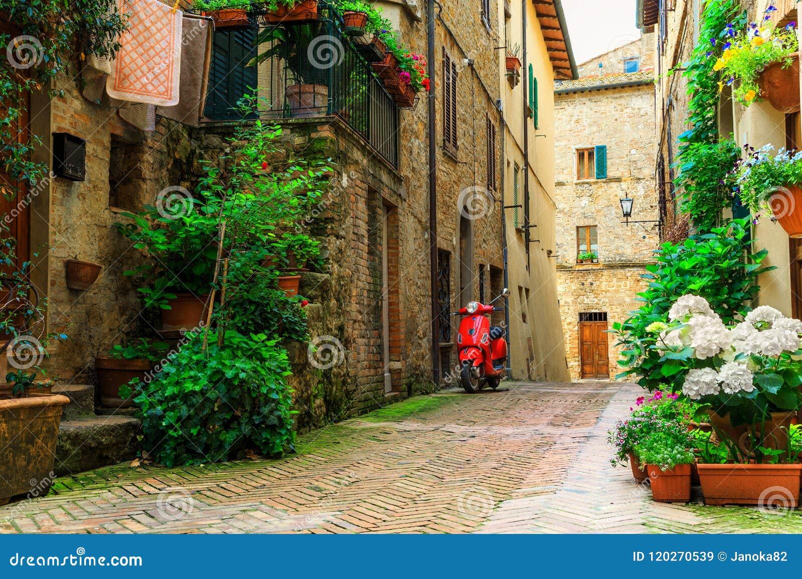Rua italiana típica com flores e o  trotinette  coloridos, Pienza, Toscânia
