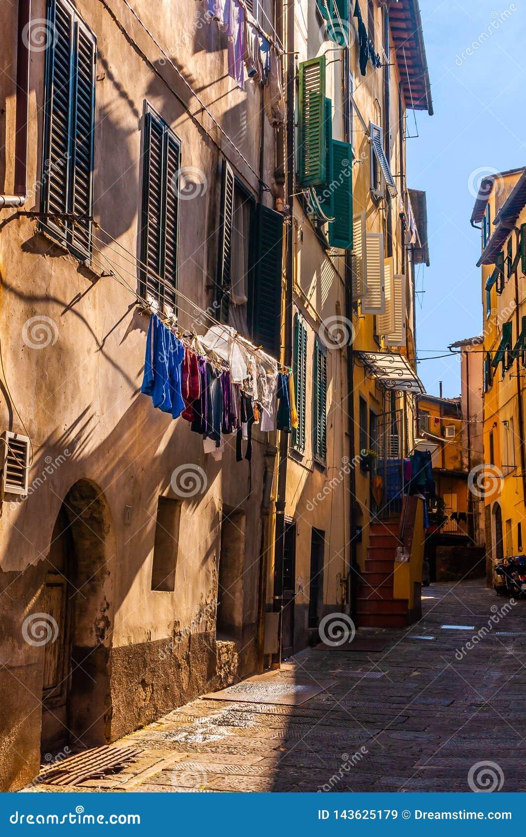 Rua pedestre pequena da cidade de Itália em parte nas sombras com secagem da roupa e de máscaras locais