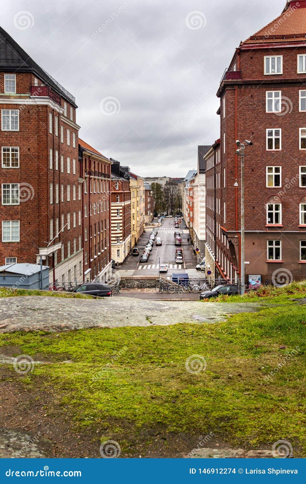 Ruas de Helsínquia com as casas bonitas do tijolo vermelho e paisagem de pedra da cidade, Helsínquia, Finlandia