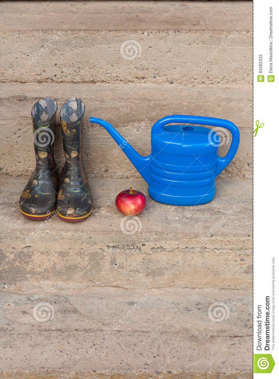 Rubber Boots, Red Apple And Small Blue Watering Can