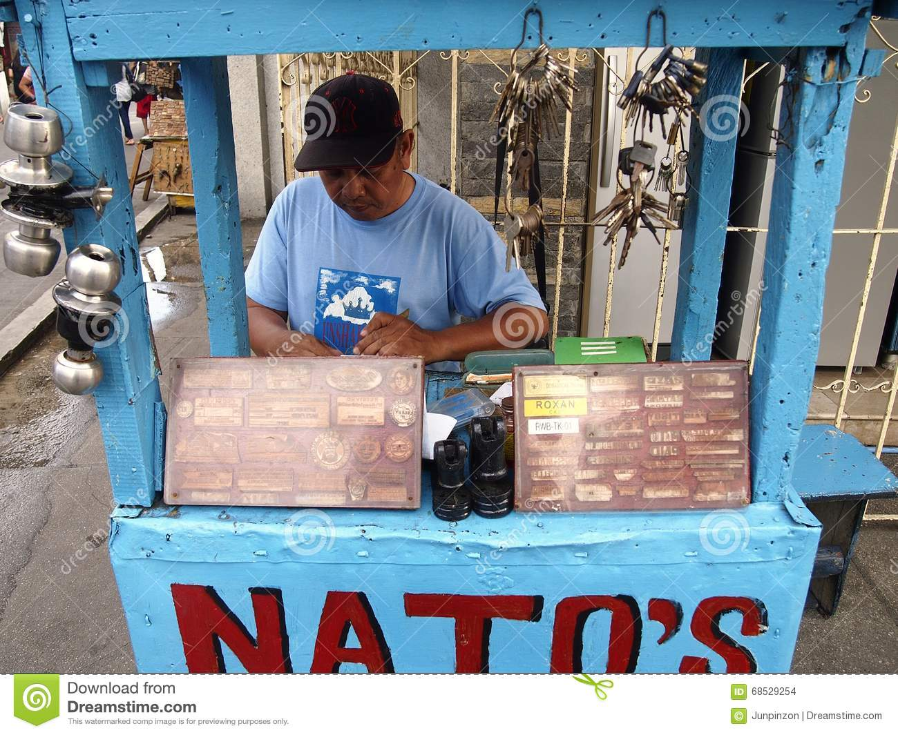 A Rubber Stamp Maker Working In His Small Stall Along A ...