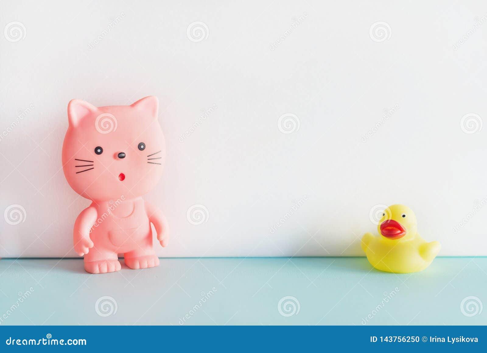 Rubberspeelgoed op blauwe en witte achtergrond Een roze rubberkat en een gele rubbereend die zich verenigen Badspeelgoed