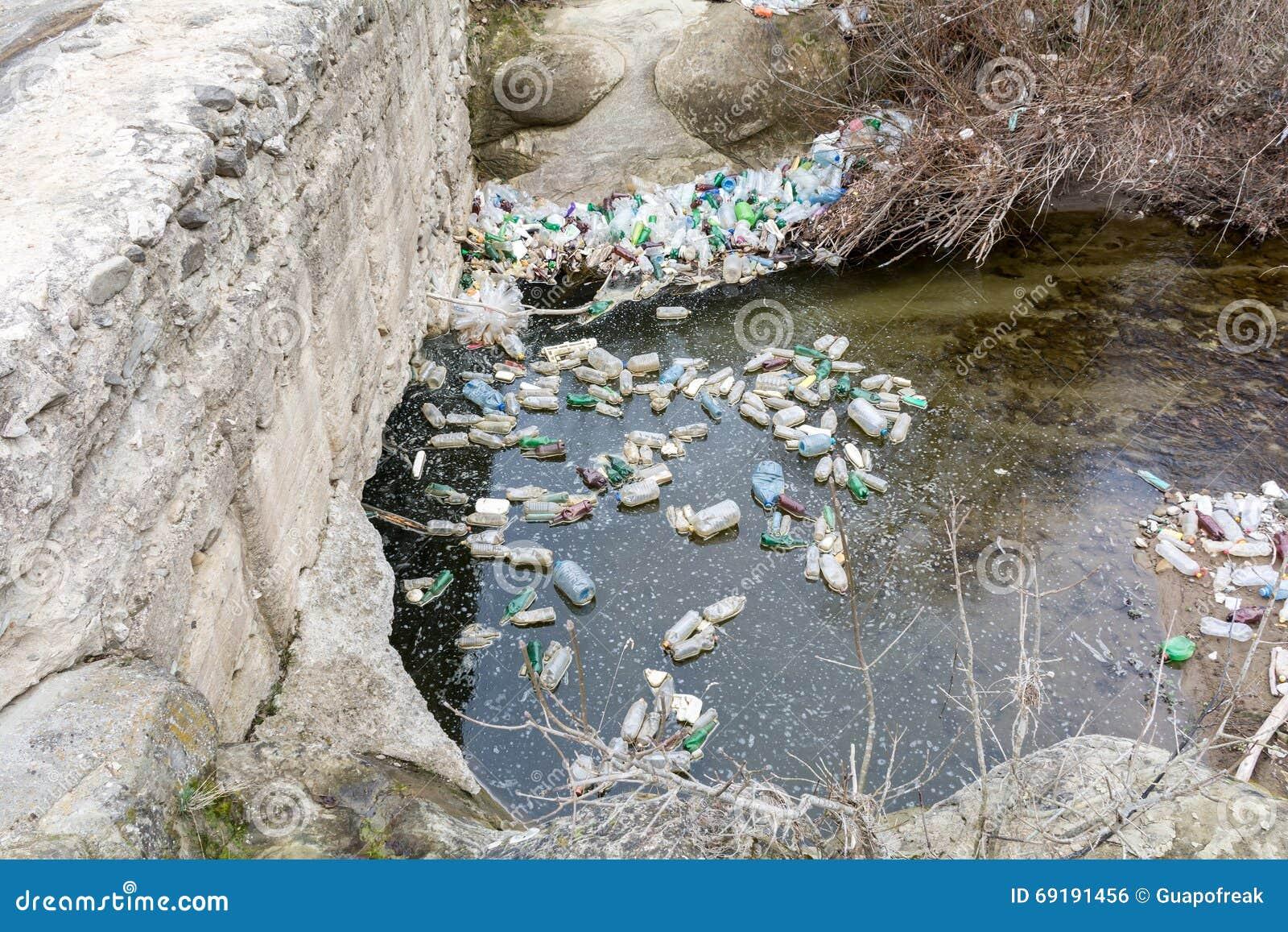 Rubbish la contaminación con el plástico y otras materias de empaquetado en el río