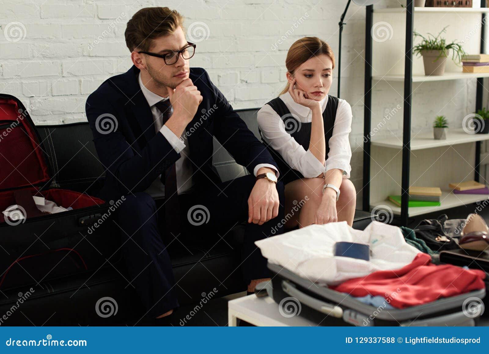 Rubbningaffärskvinna och affärsmanpar som ser på lopppåse