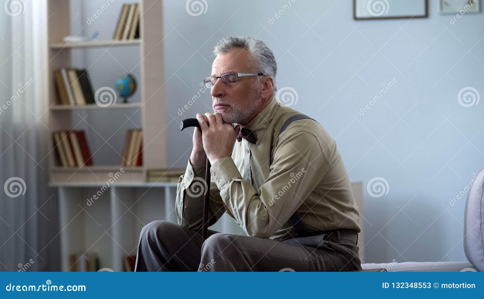Rubbninggamala mannen som lutar på den gå pinnen som tar ta sig en tupplur på middagar, ensam känsla
