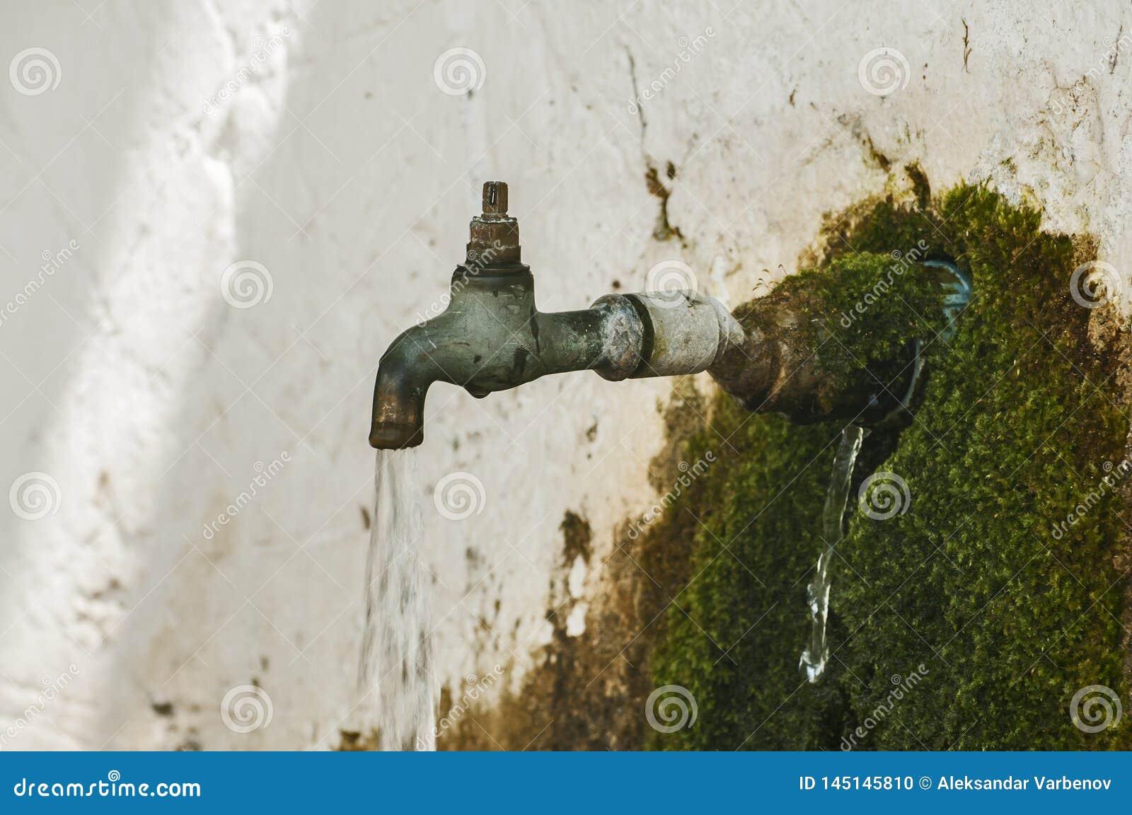 Rubinetto di acqua di rubinetto corrente stagionato obsoleto