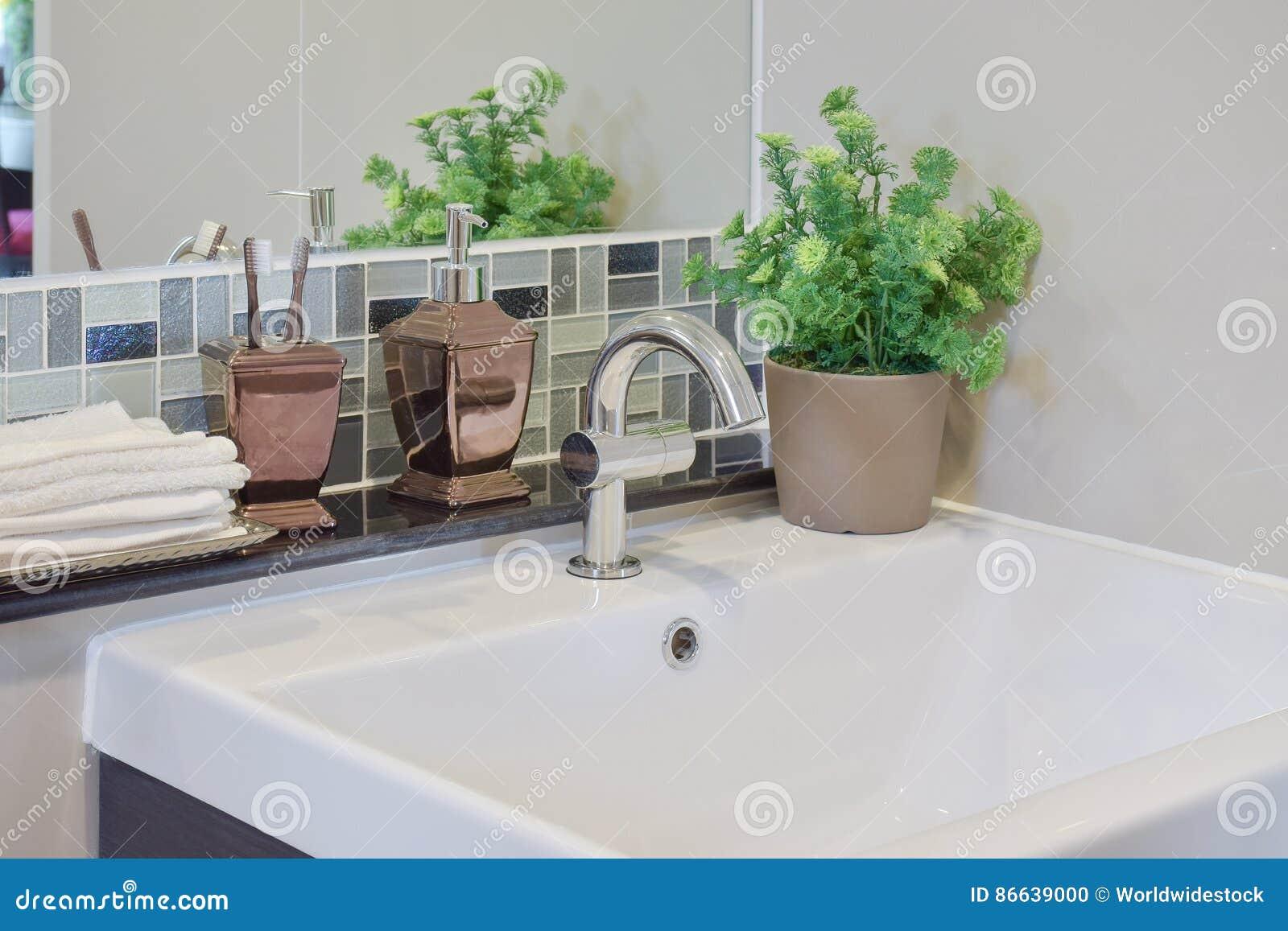 Rubinetto e lavabo con la bottiglia del sapone liquido dei dentifrici in pasta