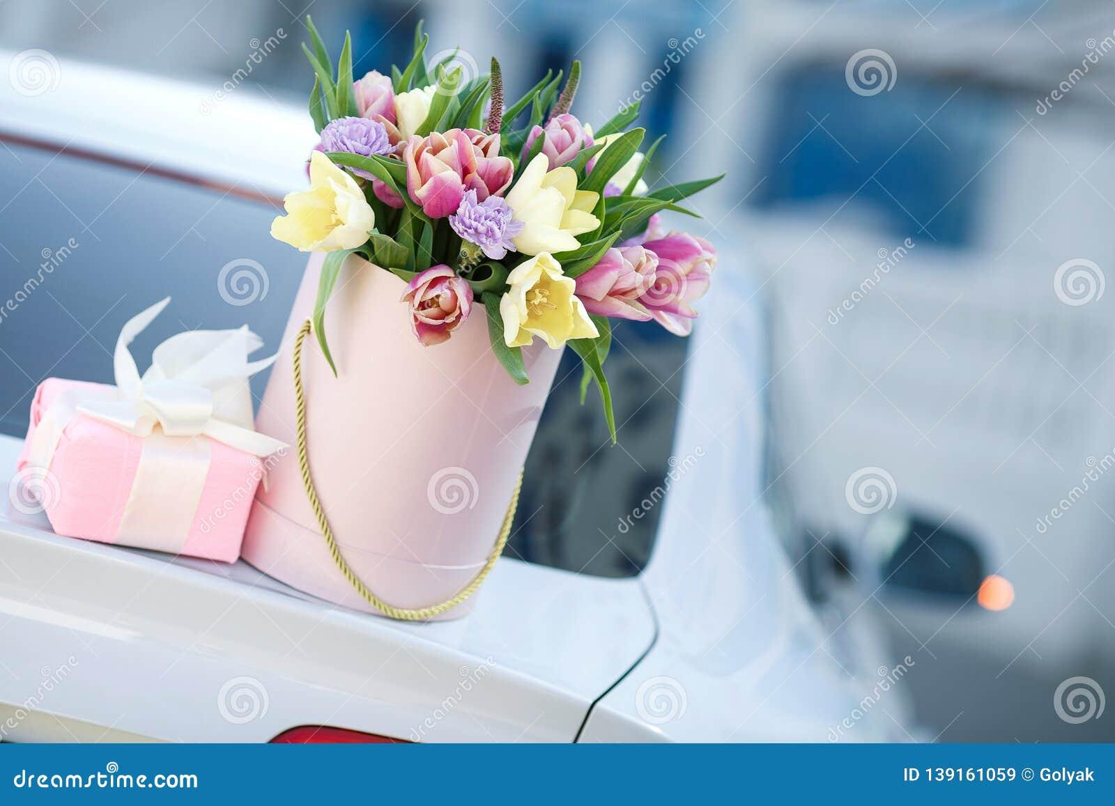 Rubio joven hermoso con el pelo ondulado al aire libre con un ramo grande de flores en una calle brillante en la ciudad