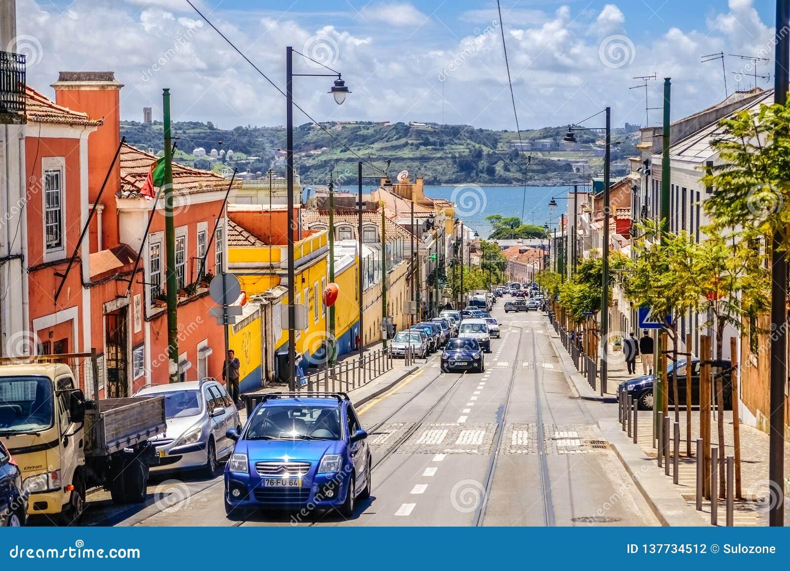 Ruch drogowy skłon ulica w Lisbon z kolorowymi budynkami wzdłuż pobocza i dennego widoku
