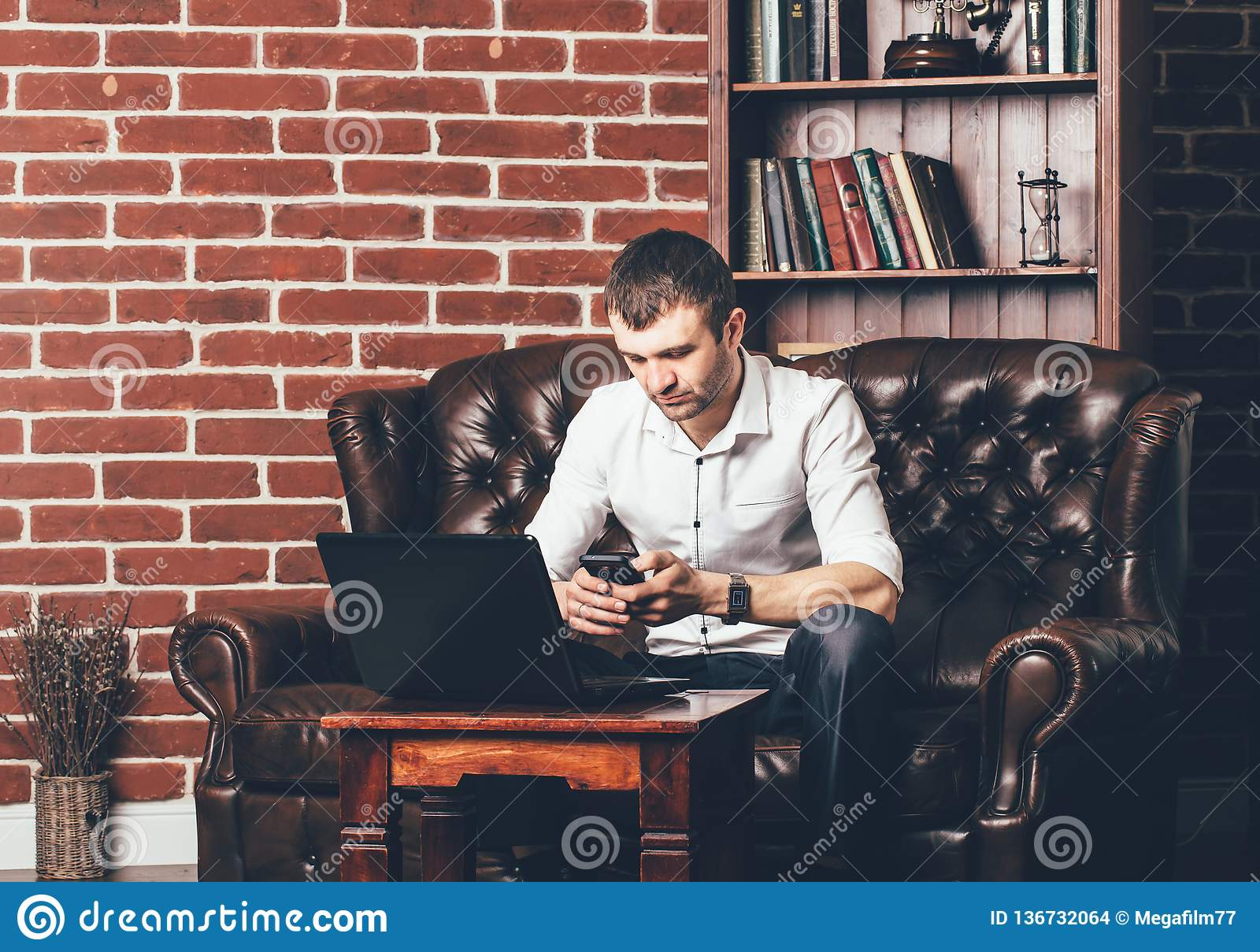Ruchliwie mężczyzna dzwoni numer telefonu Biznesmen jest w jego gabinecie za jego laptopem na tle ściana z dekoracyjnymi cegłami