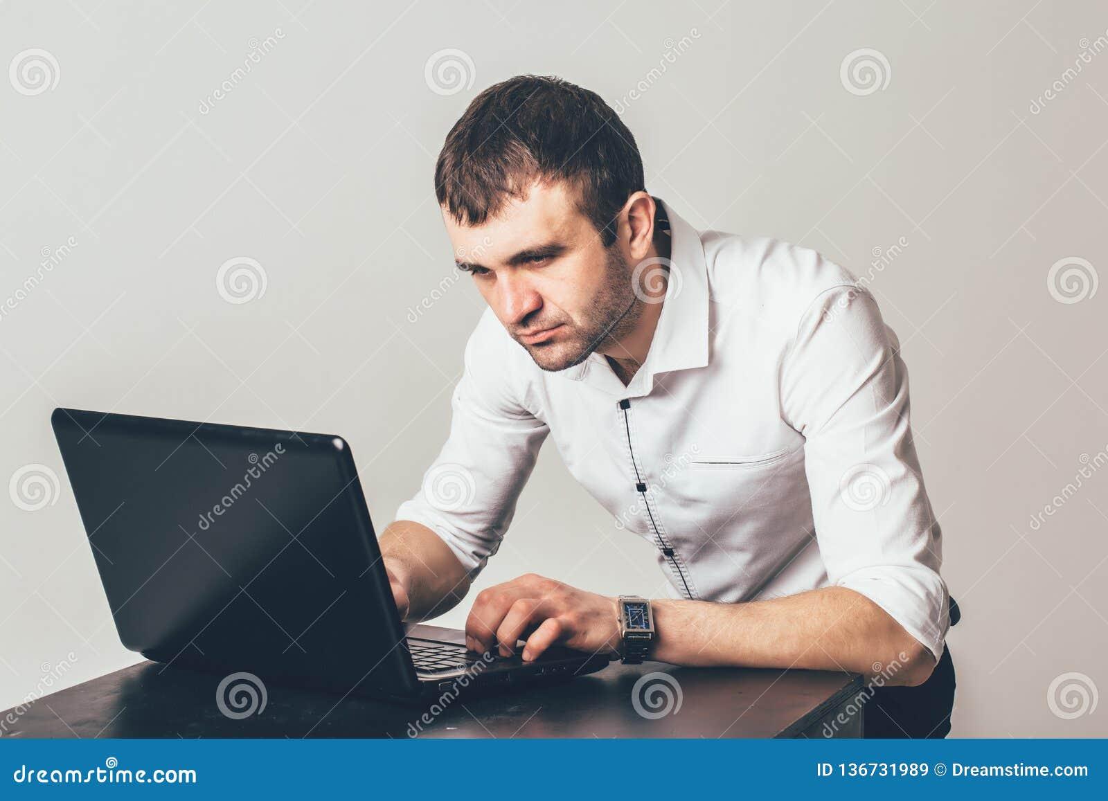 Ruchliwie mężczyzna pracuje na laptopie w biurze Biznesmen skupia się na rozwiązaniu zadania