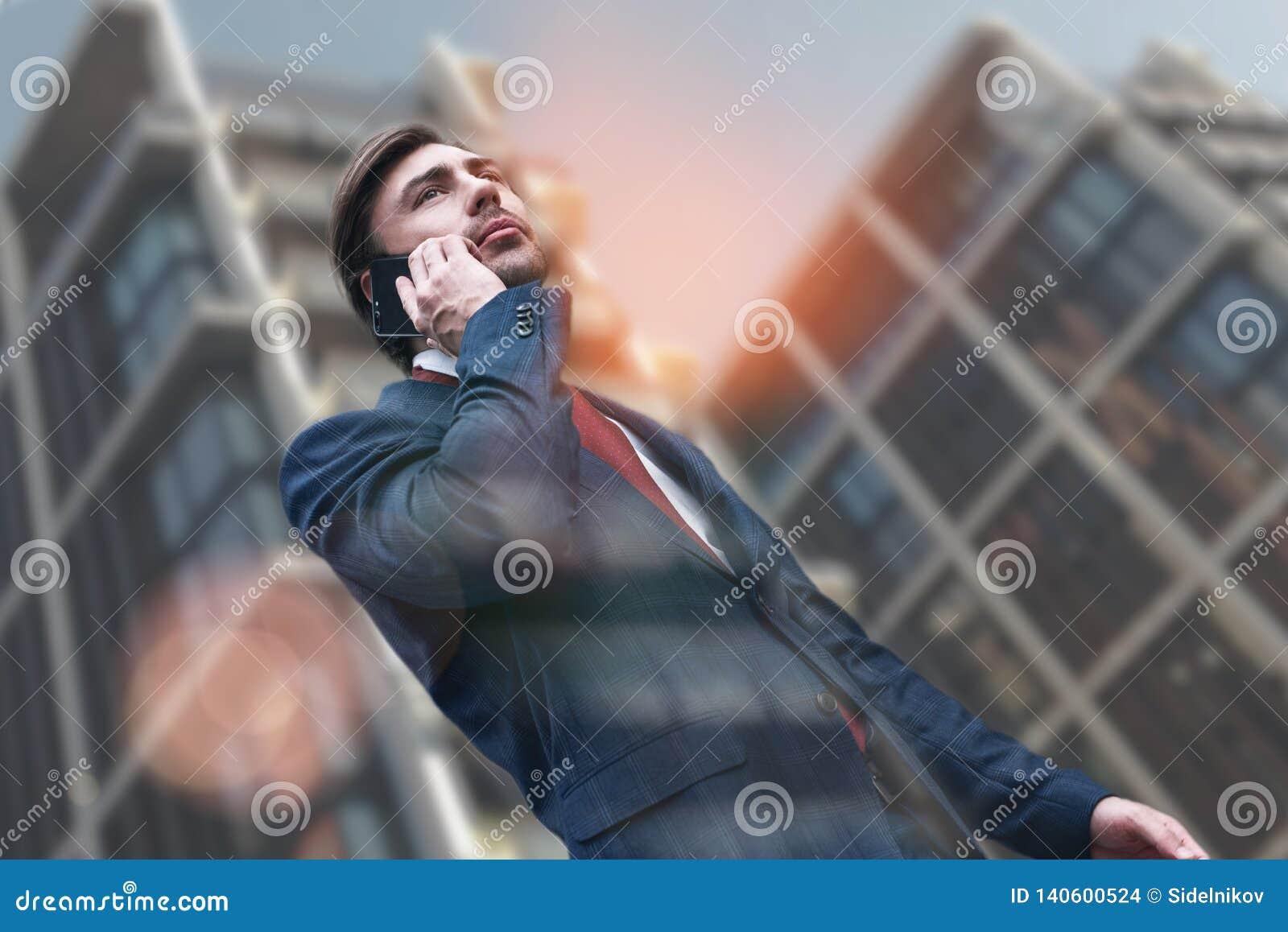 Ruchliwie ranek Atrakcyjny elegancki biznesmen opowiada na telefonie w kostiumu podczas gdy chodzący przez miasto ulic z