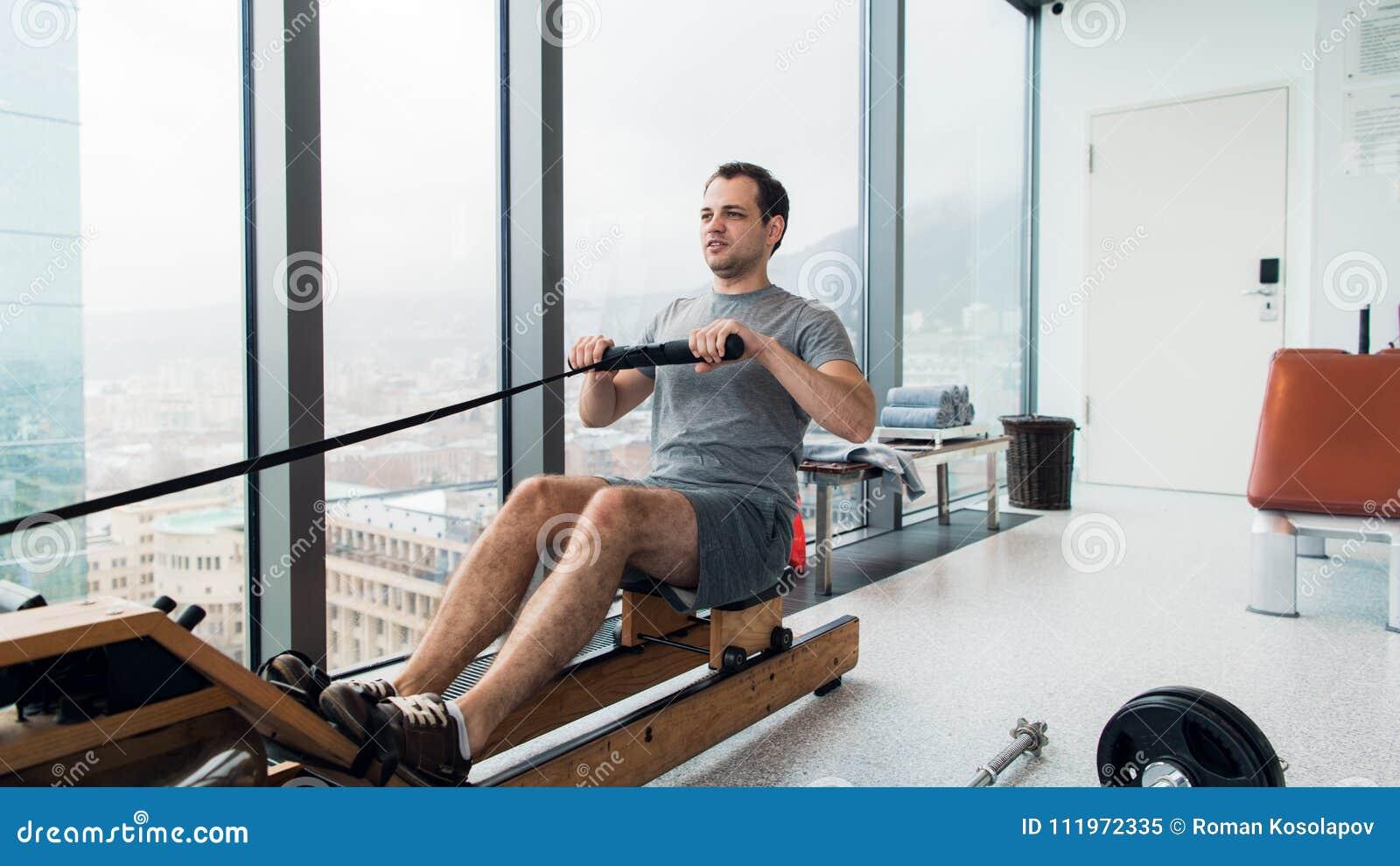 Rudern mit Energie Seitenansicht des jungen Mannes in der Sportkleidung, die Rudersport vor Fenster an der Turnhalle tut