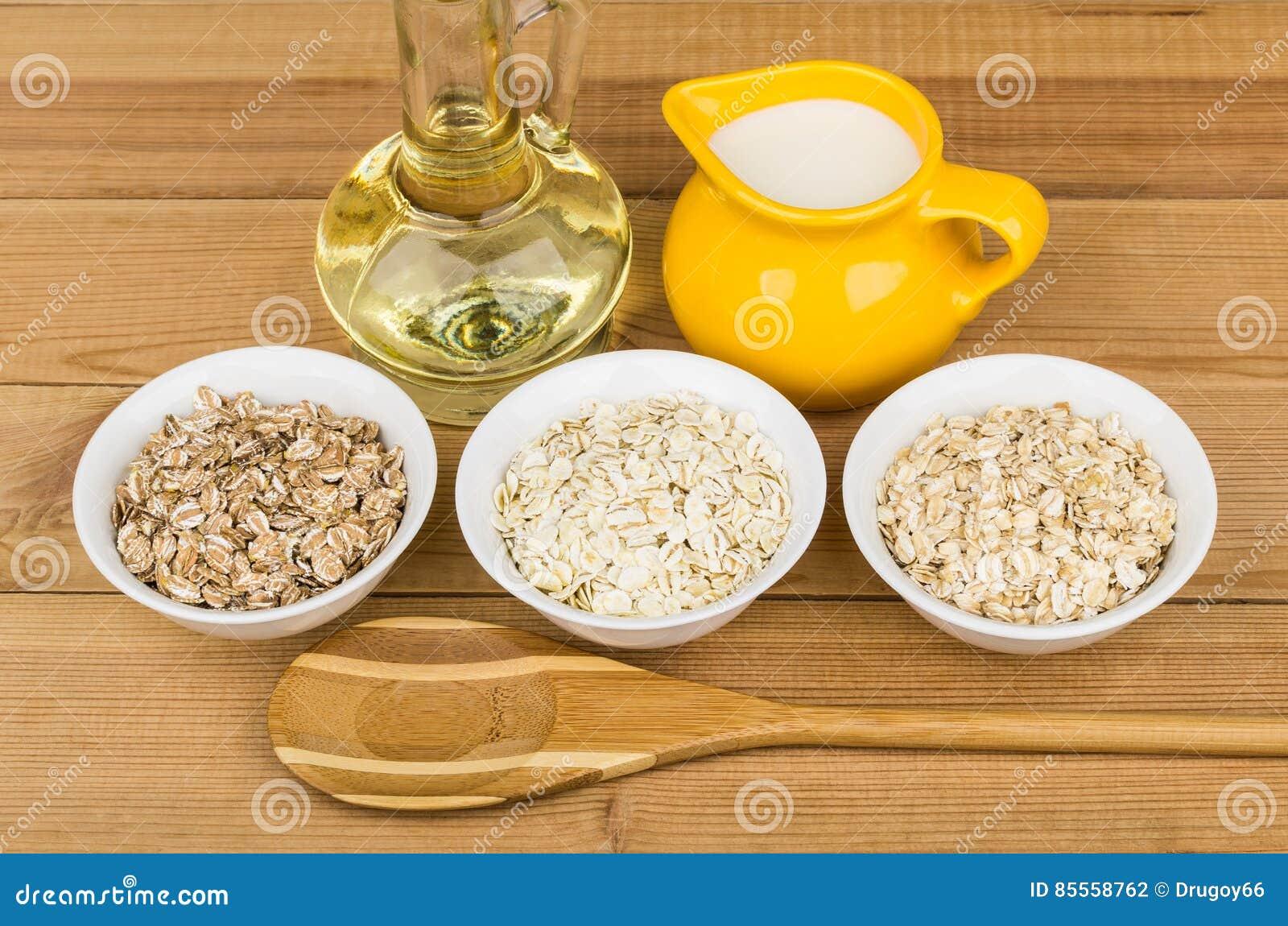 Rudern Sie Glasschüssel mit Hafer, Roggen, Gerstenflocken, Pflanzenöl