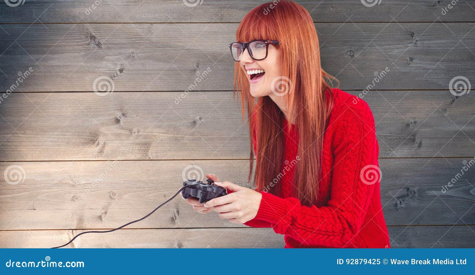 Rudzielec kobieta bawić się wideo grę przeciw drewnianej ścianie
