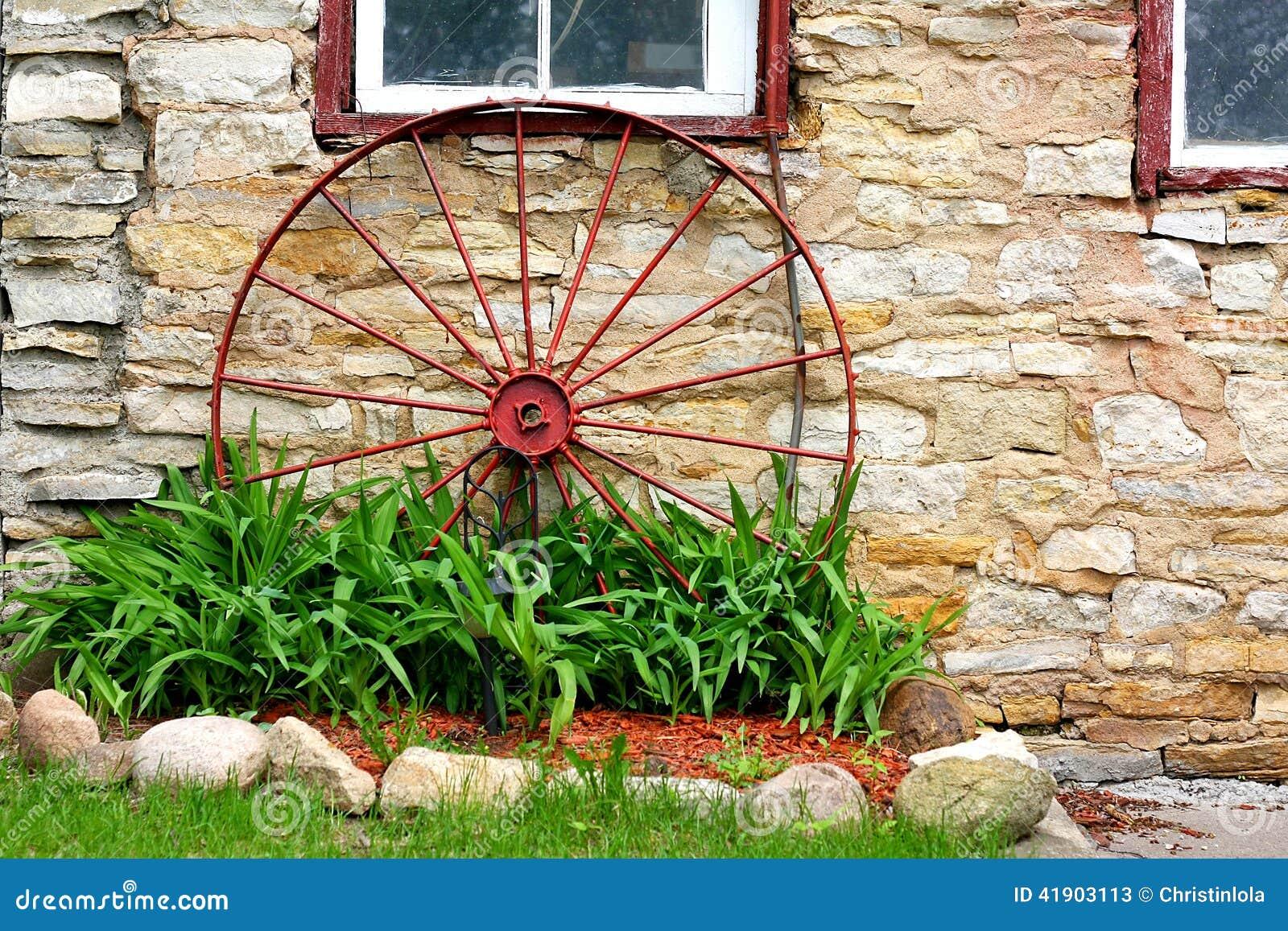 Rueda de carro vieja delante del granero de piedra